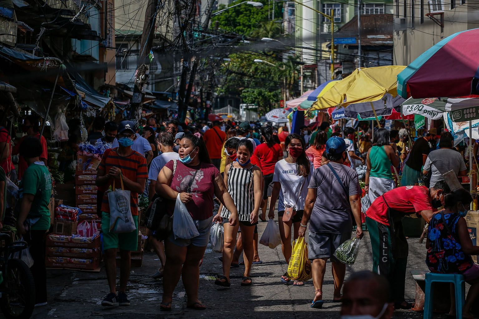 People shopping at a public market in Makati city, south of Manila, last week. The Philippine government this week allowed a host of companies to reopen in the country, but with only half their usual workforce. Malls have also reopened, but most of t