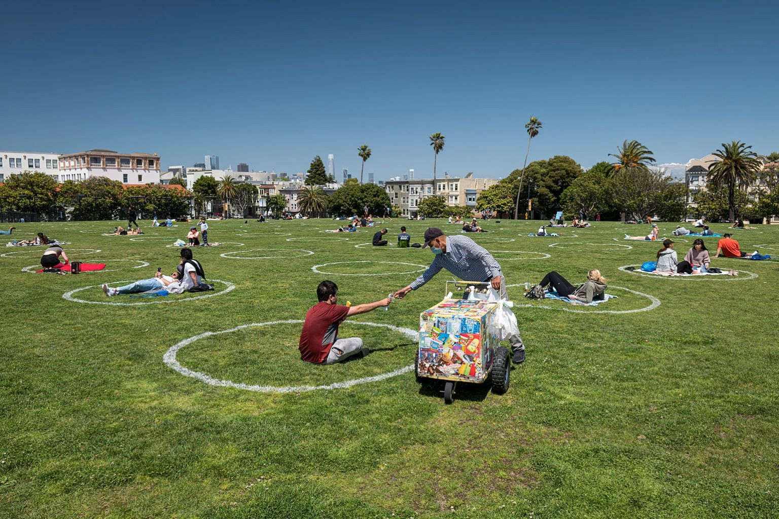 People relaxing within circles marked out on the grass to promote social distancing to curb the spread of the coronavirus in San Francisco, California, on Thursday.