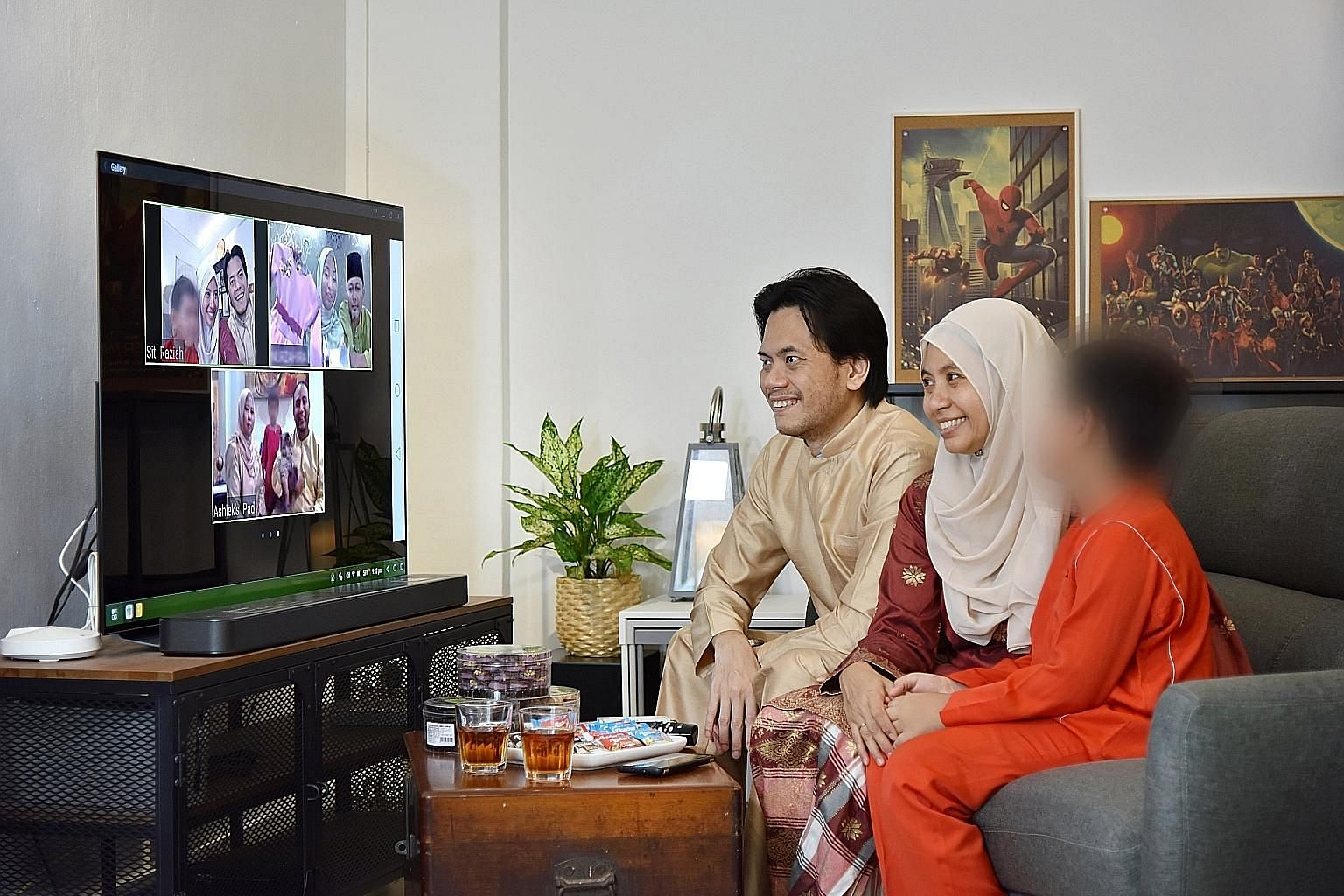 Ms Siti Raziah Raffee, her husband Kevin Woo and one of their three foster children having a Zoom call with their extended family recently. Ms Siti's cousins are also fostering children.