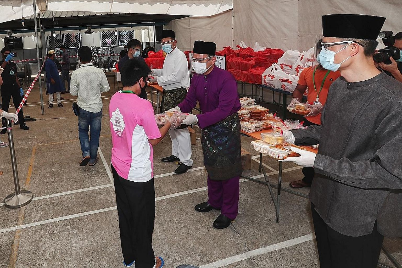 Minister of State for Manpower Zaqy Mohamad (centre), flanked by Muis chief executive Esa Masood (right) and SMCCI deputy president Abu Bakar Mohd Nor, distributing special meals and festive goodies to migrant workers at Woodlands Dormitory to mark H