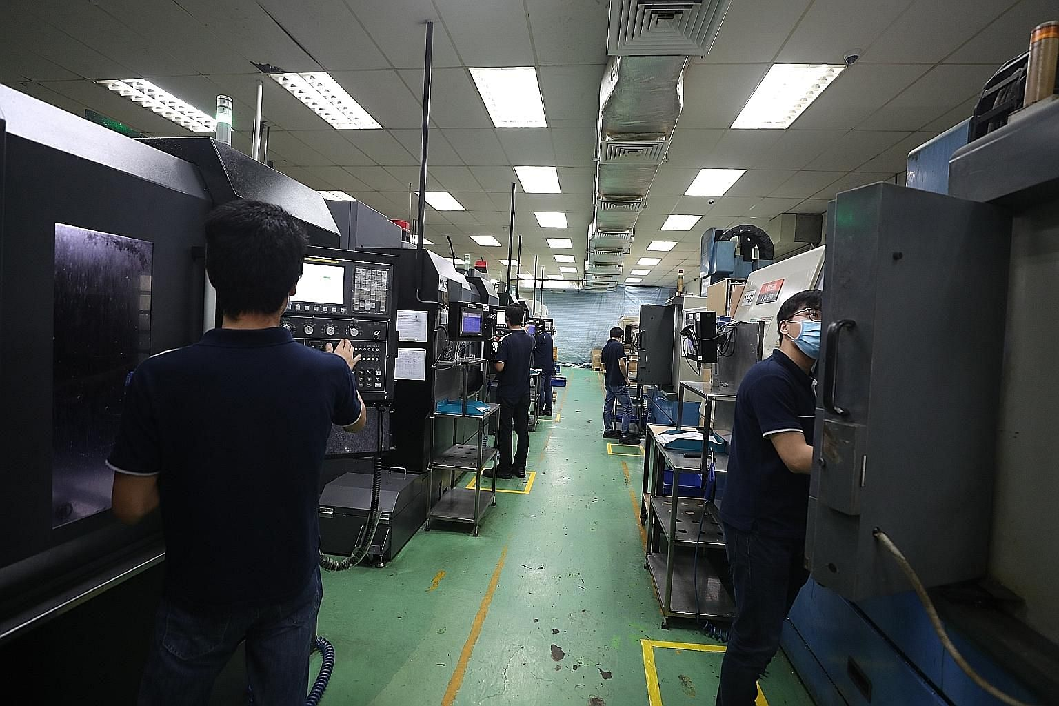Safe distancing measures in place at Shine Precision Engineering. Social distancing and contact tracing are likely to be a big part of the day-to-day operations in firms for the long haul, says the writer. ST PHOTO: TIMOTHY DAVID