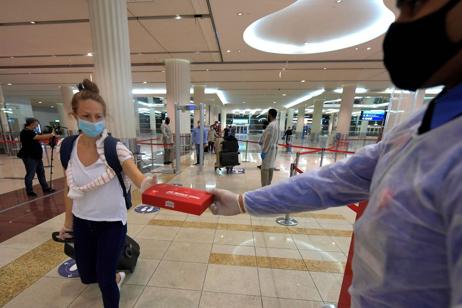 An Emirates passenger receiving a box of masks and gloves at Dubai airport on Friday. Observers say the industry is looking at a time lag of three years at least before business returns to pre-Covid days.