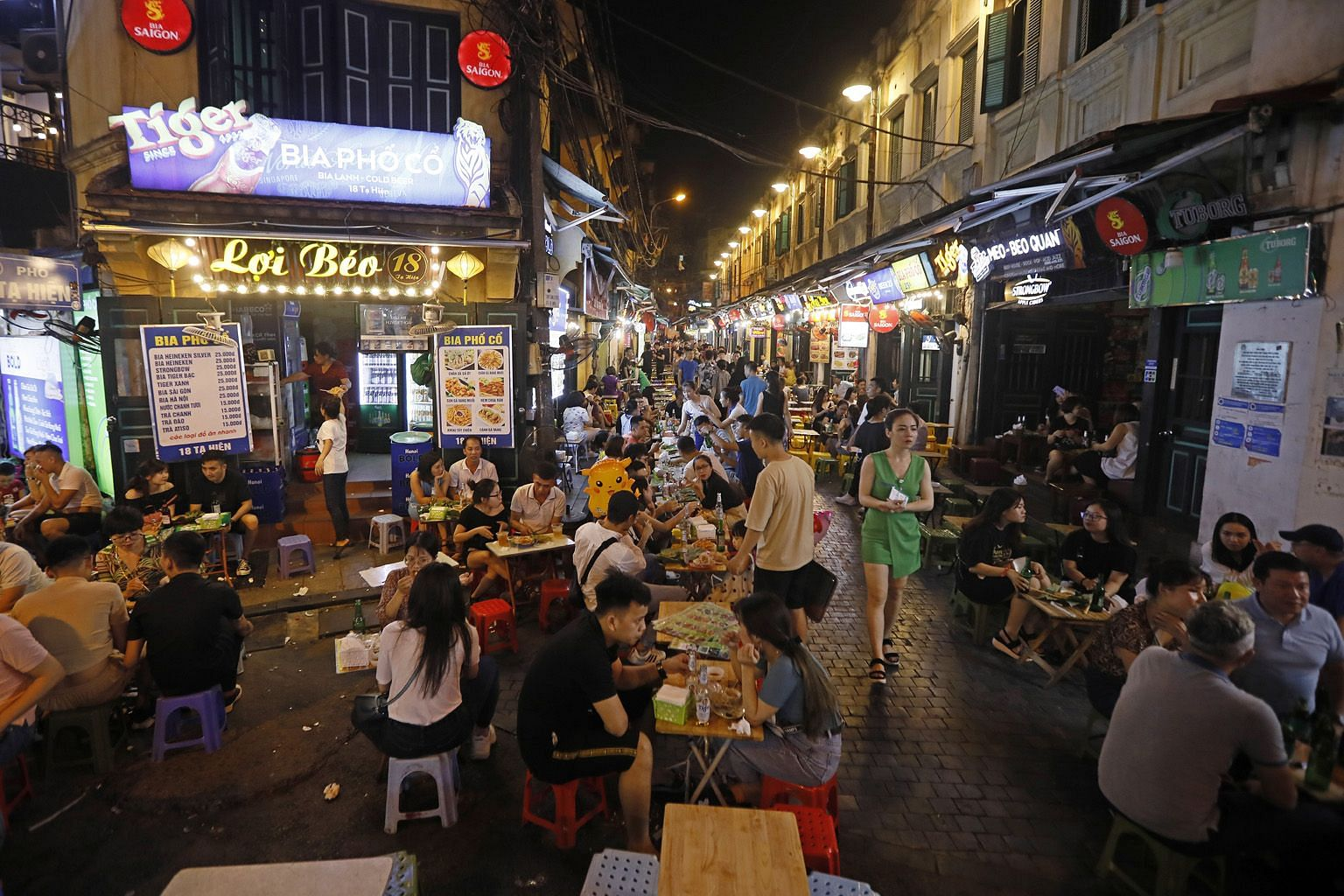 """Left: People enjoying a drink at the Bia Hoi Corner in Hanoi's old quarter on Friday. The government this month flagged off a """"Vietnamese people travel to Vietnam destinations"""" campaign."""