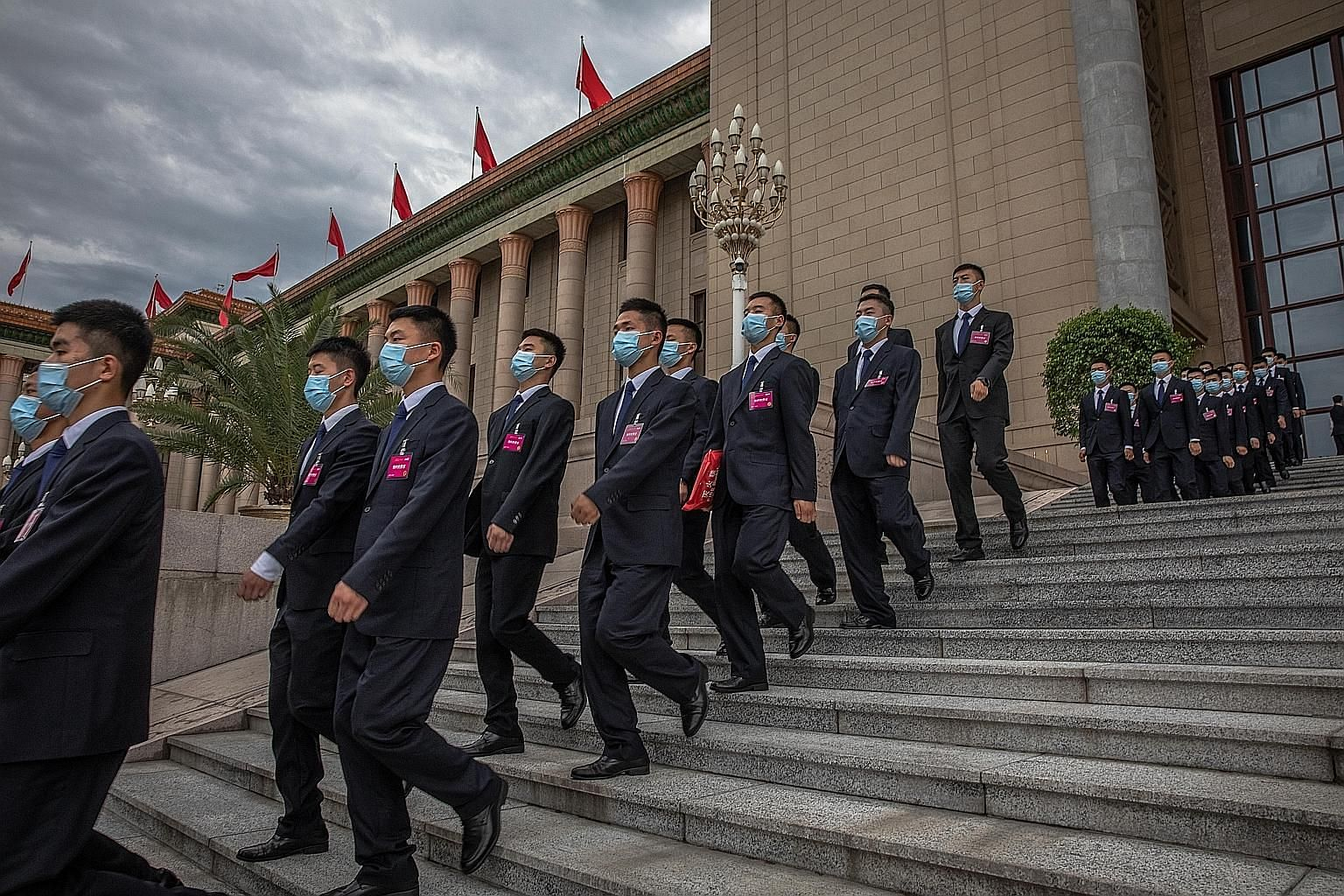Security officials marching after the second plenary session of China's National People's Congress at the Great Hall of the People in Beijing, where the country's top prosecution body presented its annual report yesterday.