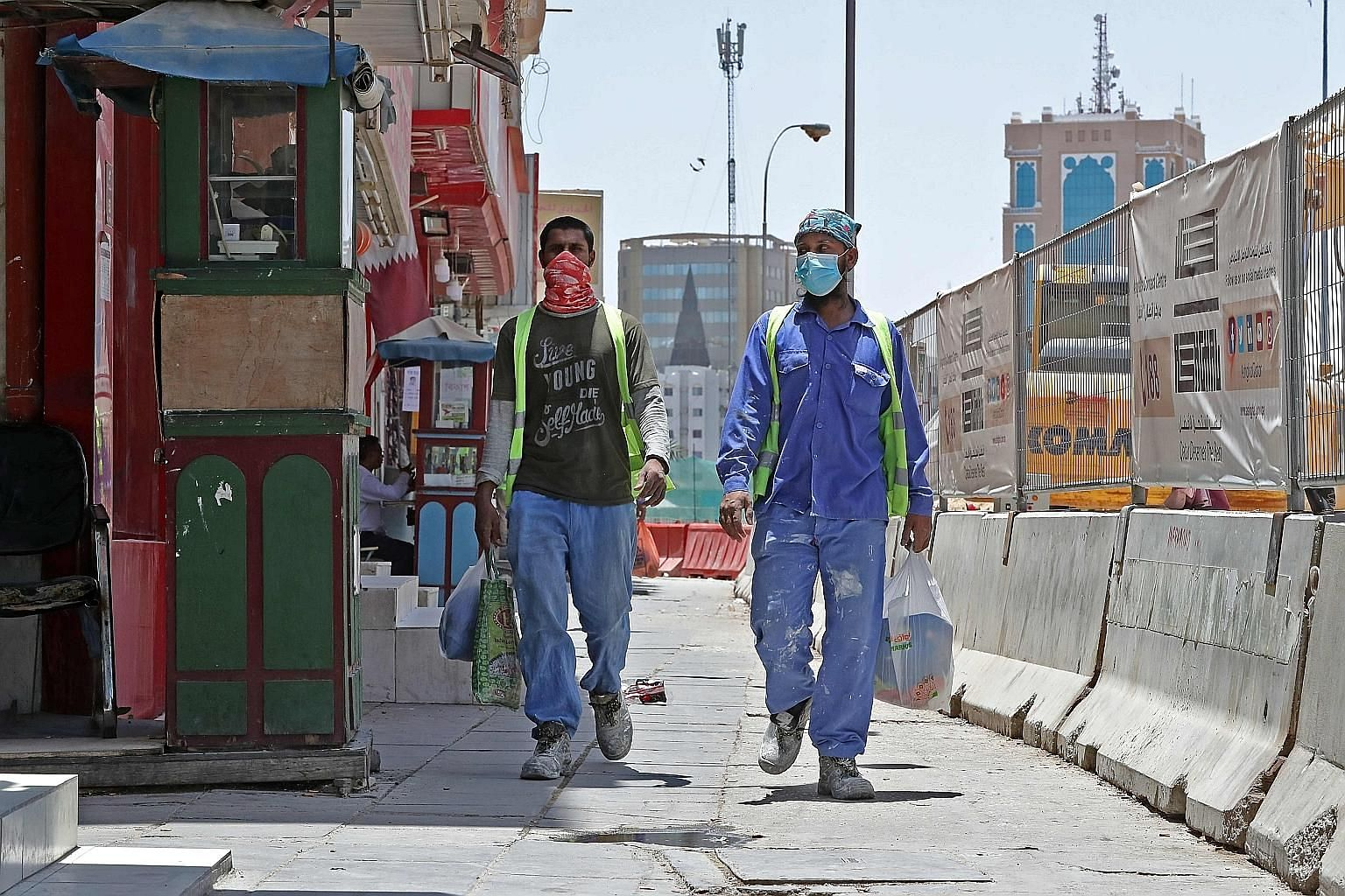Workers wearing protective masks on a street in Doha, Qatar, on May 17. Like in Singapore, the outbreak in Qatar has centred on its foreign workers, who outnumber Qataris in the workforce by nearly 20 to one. Qatar's ambition to host the World Cup ha