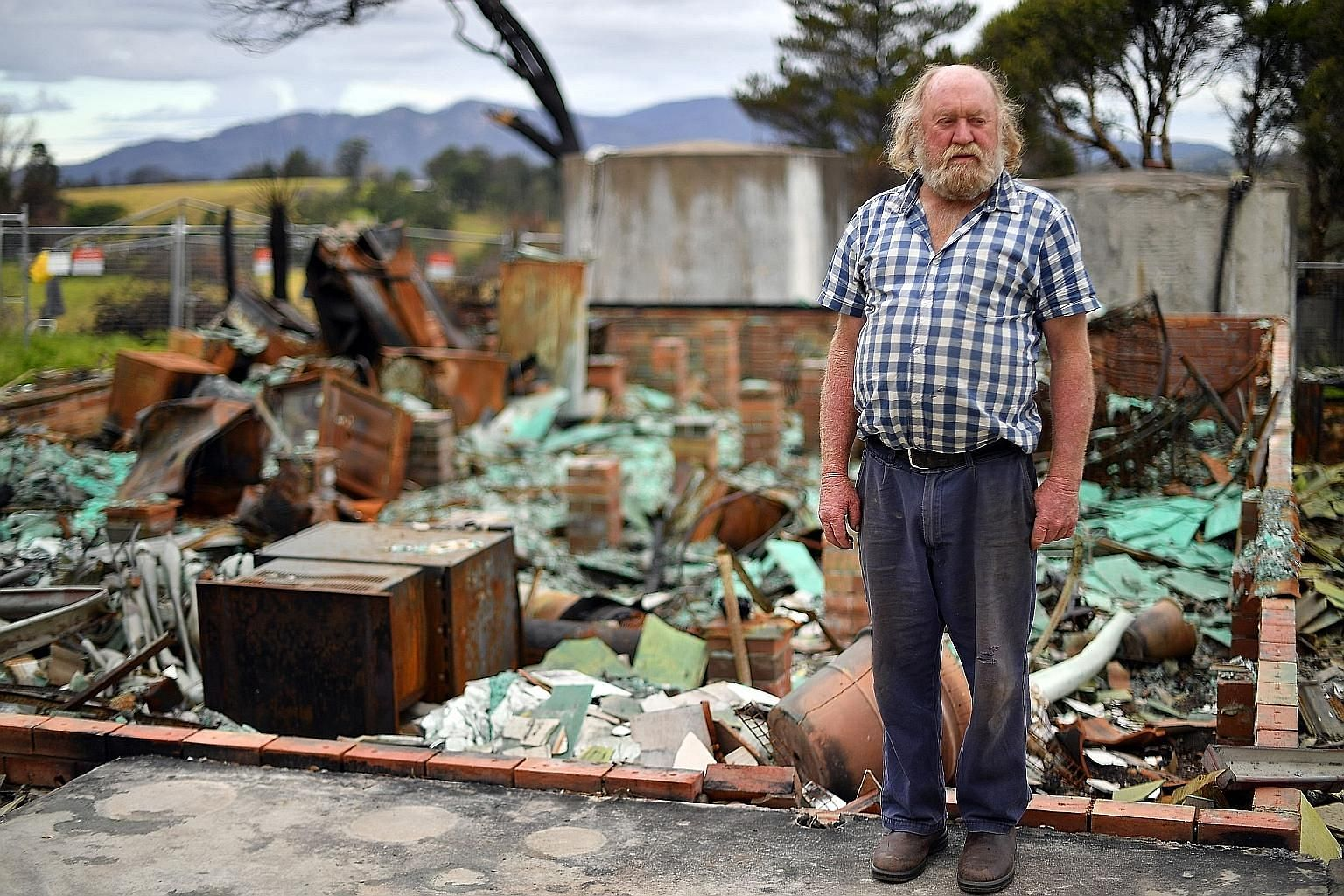 """Recovery has been """"slow and difficult"""" for many, says 66-year-old Wayne Keft, standing in front of the ruins of his house last Thursday. His home near Cobargo was destroyed when """"a fireball went through the front of the house"""". Ms Anita Lawrence, 51,"""