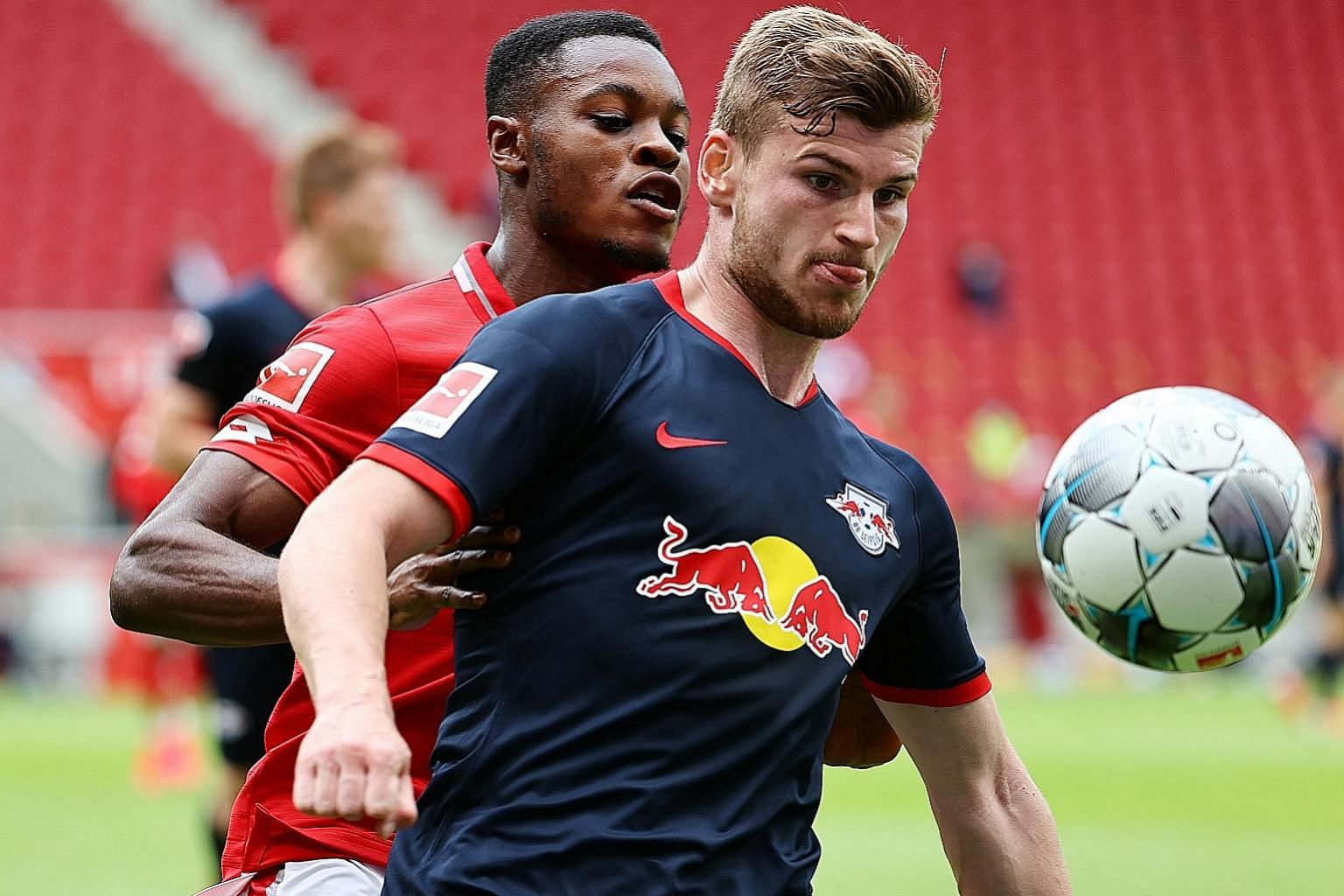 Leipzig's Timo Werner, getting some close attention from his Mainz marker Bote Baku during their match on Sunday. The Germany international netted a hat-trick in the 5-0 win to take his season's league tally to 24.