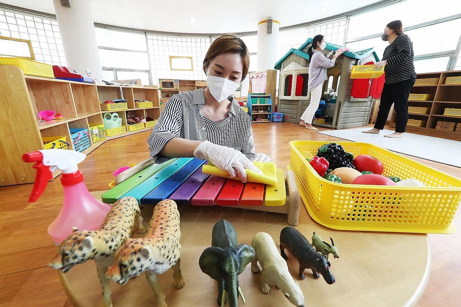 Teachers disinfecting toys at Hanil Kindergarten in Suwon, South Korea, yesterday. The country's second phase of school reopening begins today, with 2.37 million students, including kindergarteners and elementary school pupils, set to return. Many pa