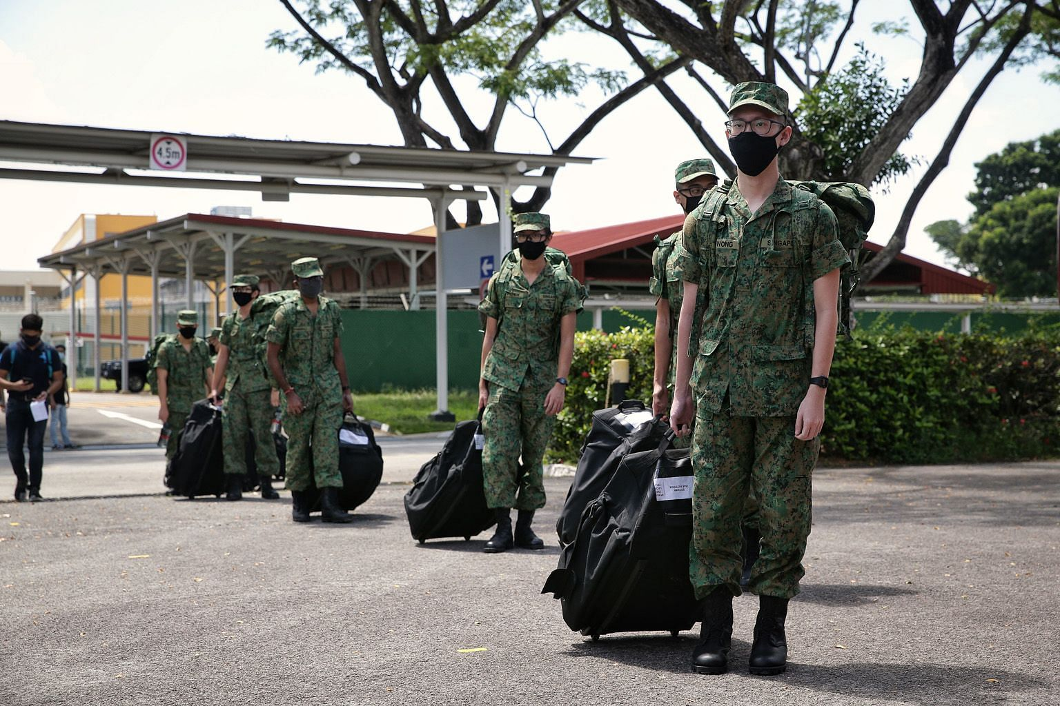 Singapore Armed Forces recruits observing safe distancing yesterday as they headed for buses taking them to the SAF Ferry Terminal. ST PHOTO: KEVIN LIM