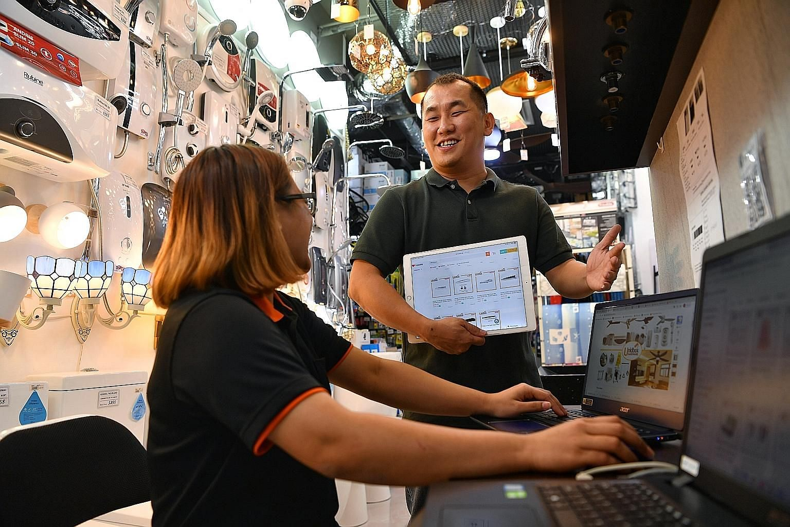 Mr Wong Hing Kong, director of Unidbox Hardware, with employee Sharon Keong, who is in charge of e-commerce, at the firm's Upper Serangoon Road outlet. The hardware store has seen a boost in sales because of e-commerce. Mr Wong went for digitalisatio