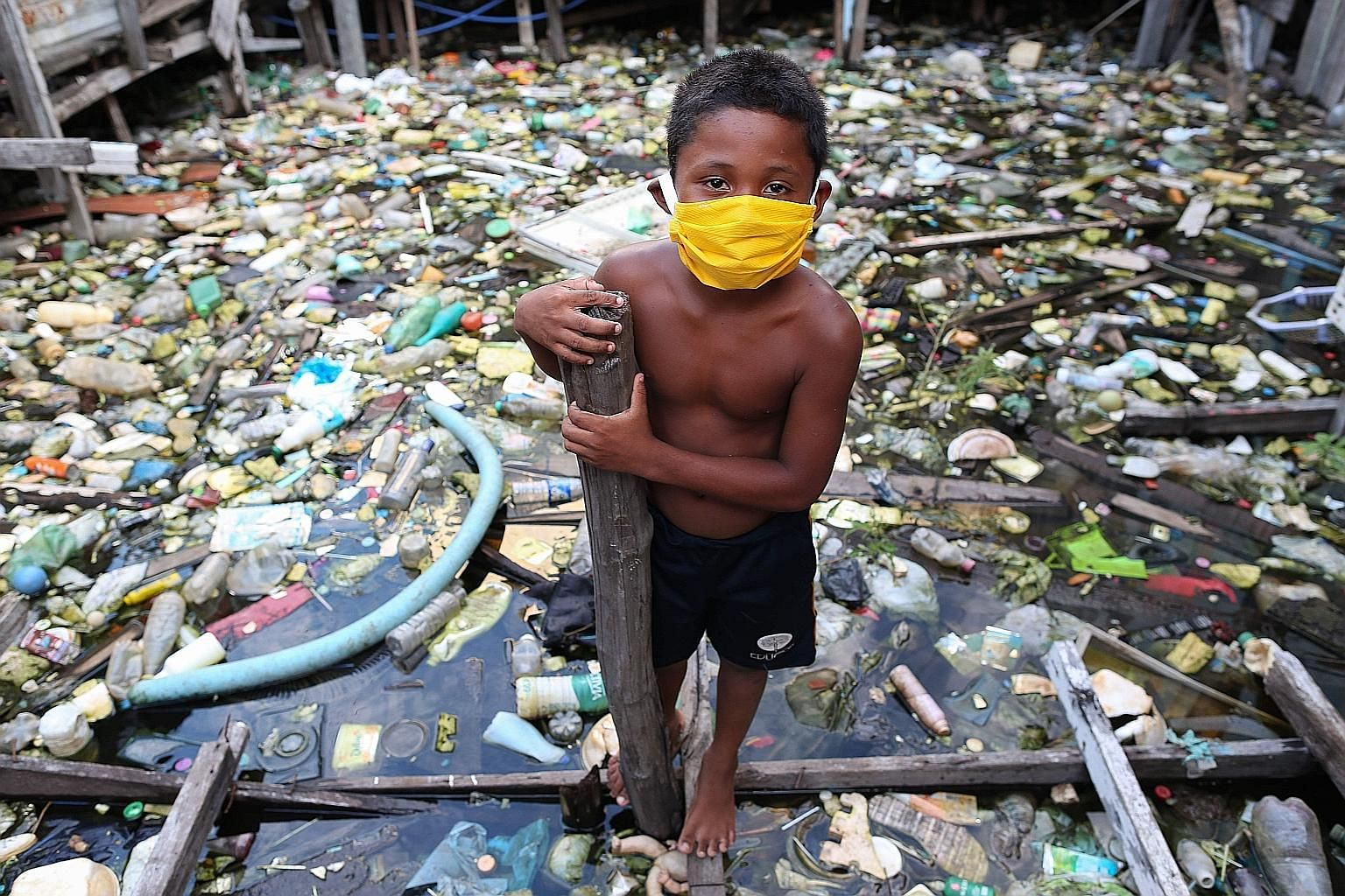 A boy from the Educandos riverside community in Manaus, the Amazon, on Tuesday. As Brazil's daily death rate became the world's highest on Monday, a University of Washington study warned that the country's total death toll could climb five-fold to 12