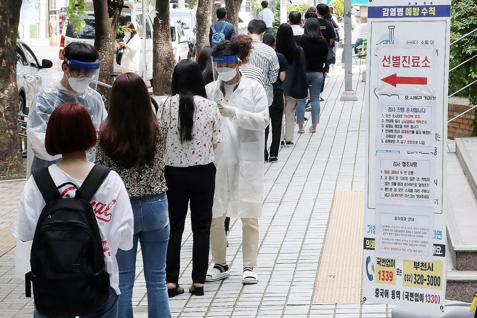 People waiting in line to be tested for coronavirus at an outdoor clinic in Bucheon, South Korea, yesterday. The new cases are mostly centred in the Seoul metropolitan area where half the South Korean population lives.