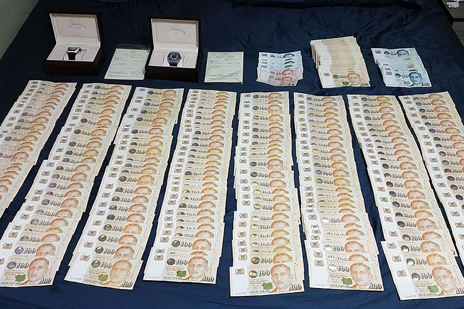 Two watches and more than $81,000 in cash were seized from Chee Jian Rong's home. He allegedly duped a foreign distribution firm.