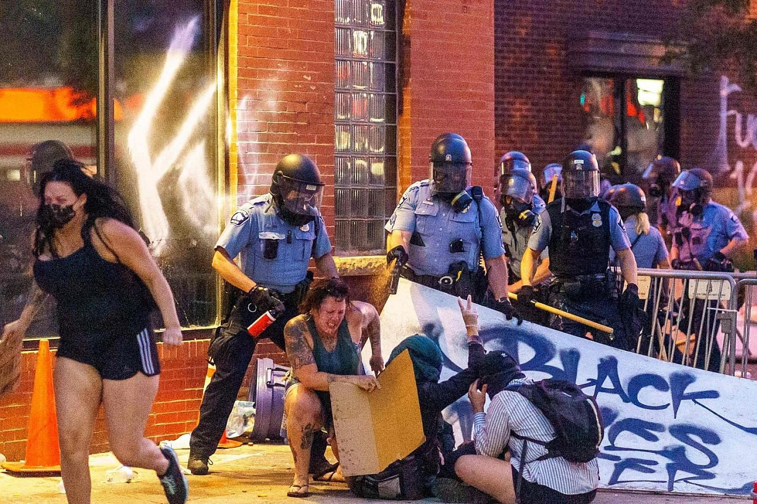 Police removing barricades set up by protesters outside the Third Police Precinct in Minneapolis on Wednesday. Left: Police in Minneapolis using pepper spray on protesters during a demonstration outside the Third Police Precinct on Wednesday over the