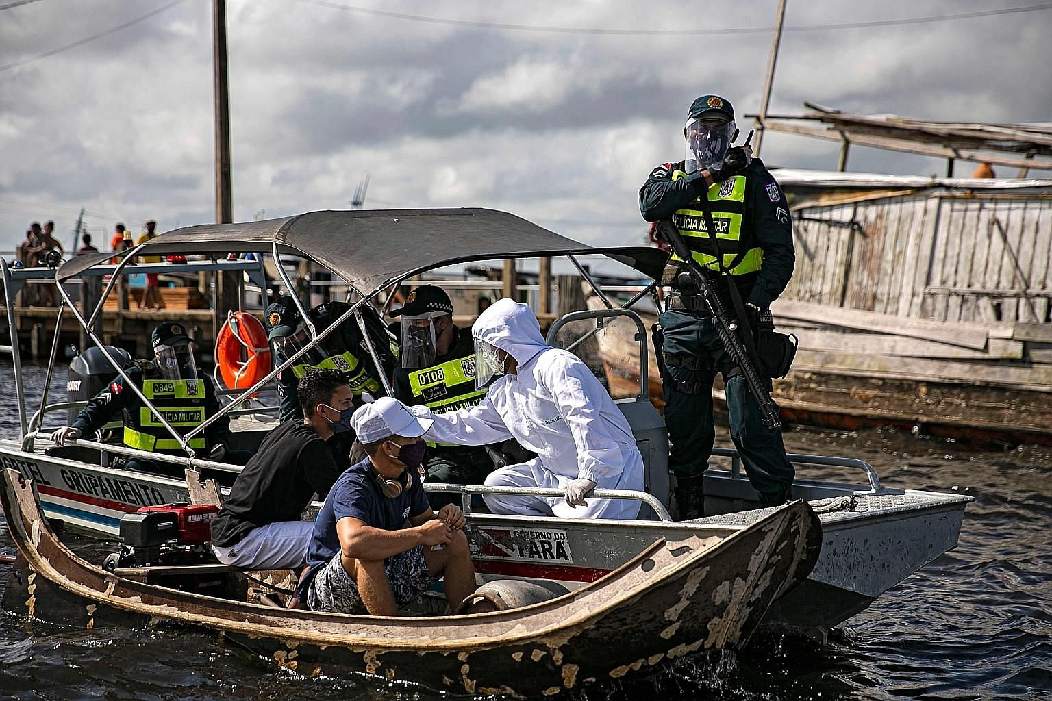 A government medical worker, in a joint operation with military police, checking the temperature of a passenger on a boat in Brazil's Para state earlier this week. Most state governments in the country have stuck to the World Health Organisation's gu