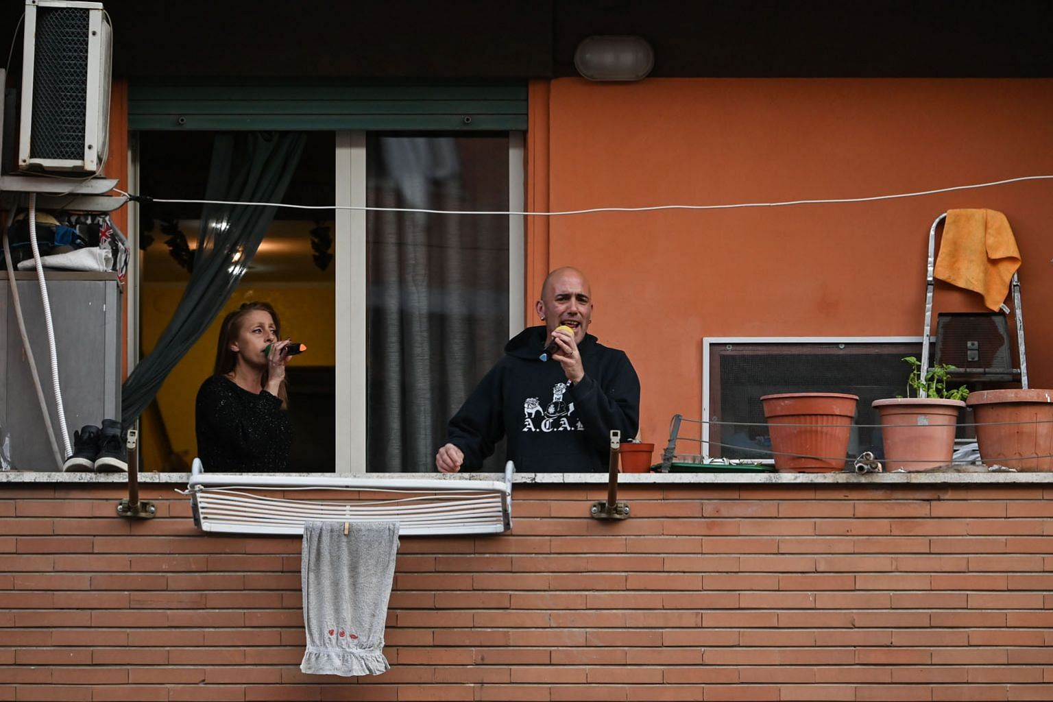 "People singing from their balcony during a flash mob in Rome's Magliana district in March. Amid strict lockdowns in Italy, flash mobs were circulated on social media to make people ""gather"" on balconies at certain hours, to play music or to get a rou"