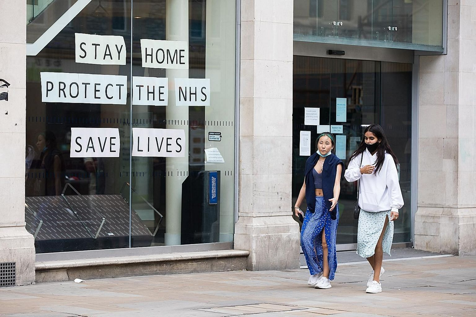 """People walking past a Barclays branch in Oxford, England, on Wednesday. At earlier stages of the outbreak, there was a strong case for a blunt, one-size-fits-all message: """"Stay at home, save lives."""" But preventing a second wave as countries reopen ca"""