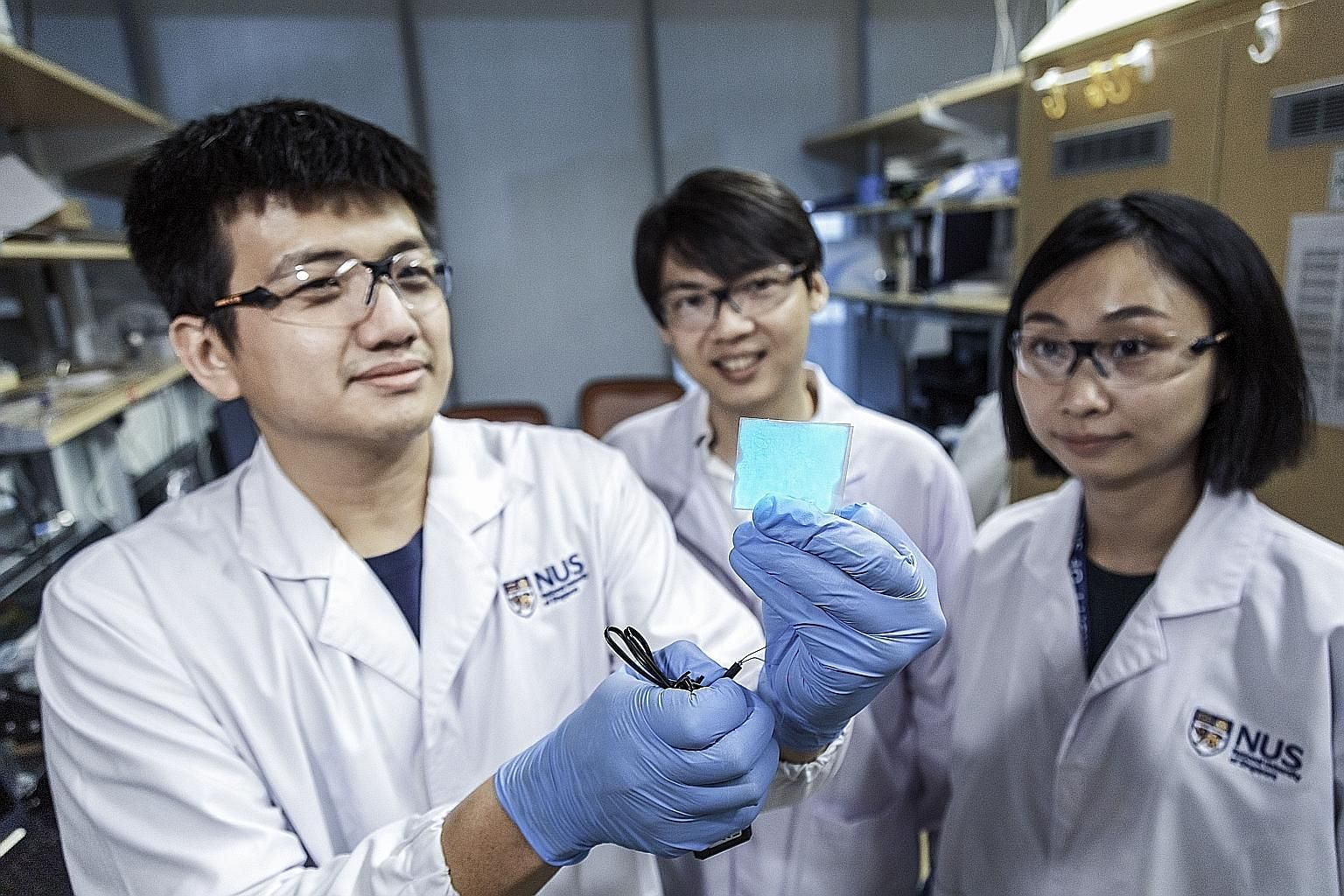 Assistant Professor Benjamin Tee (centre), who leads the NUS research team that is behind the supermaterial, with two team members - doctoral student Wang Guanxiang, who is holding up a sample of the new material, and research fellow Tan Yu Jun.