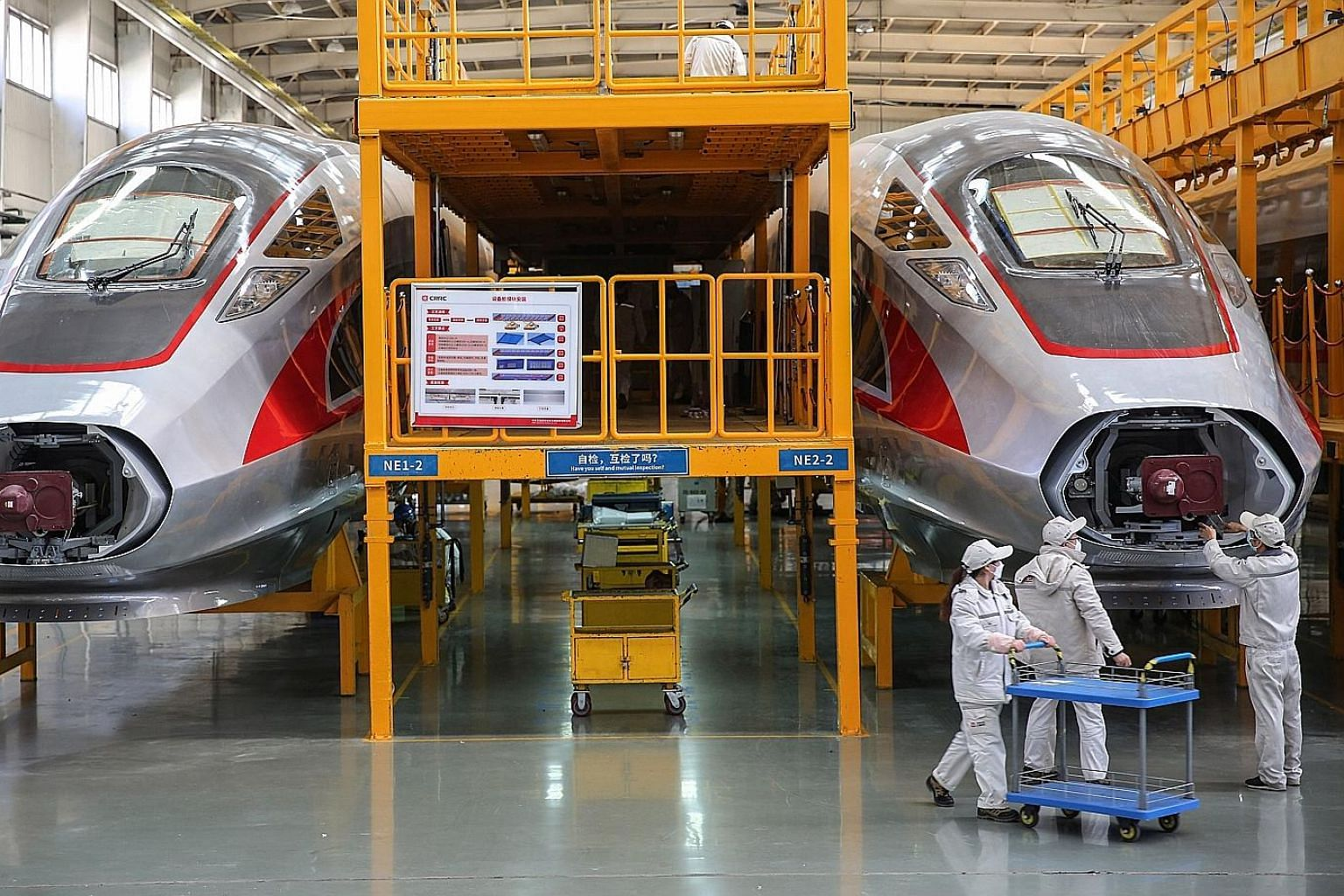 Workers checking on newly made bullet trains at a factory in Qingdao in China's eastern Shandong province in March. China's factory activity unexpectedly returned to growth last month, but with many trading partners still restricted due to the corona