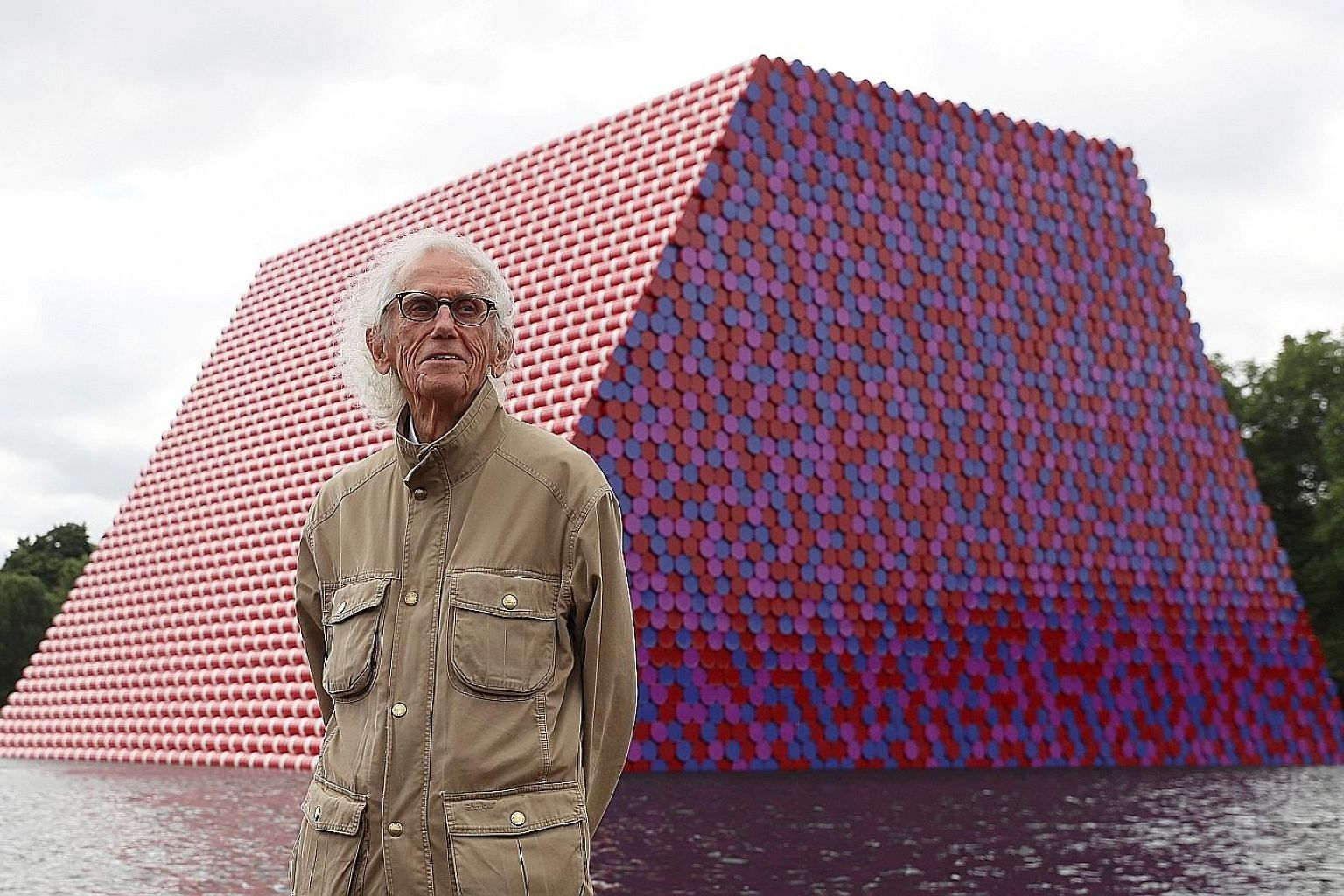 Artist Christo with his artwork Mastaba (left) built on The Serpentine lake in London, in 2018. His grand projects included wrapping the Reichstag in Berlin (above), in 1995.