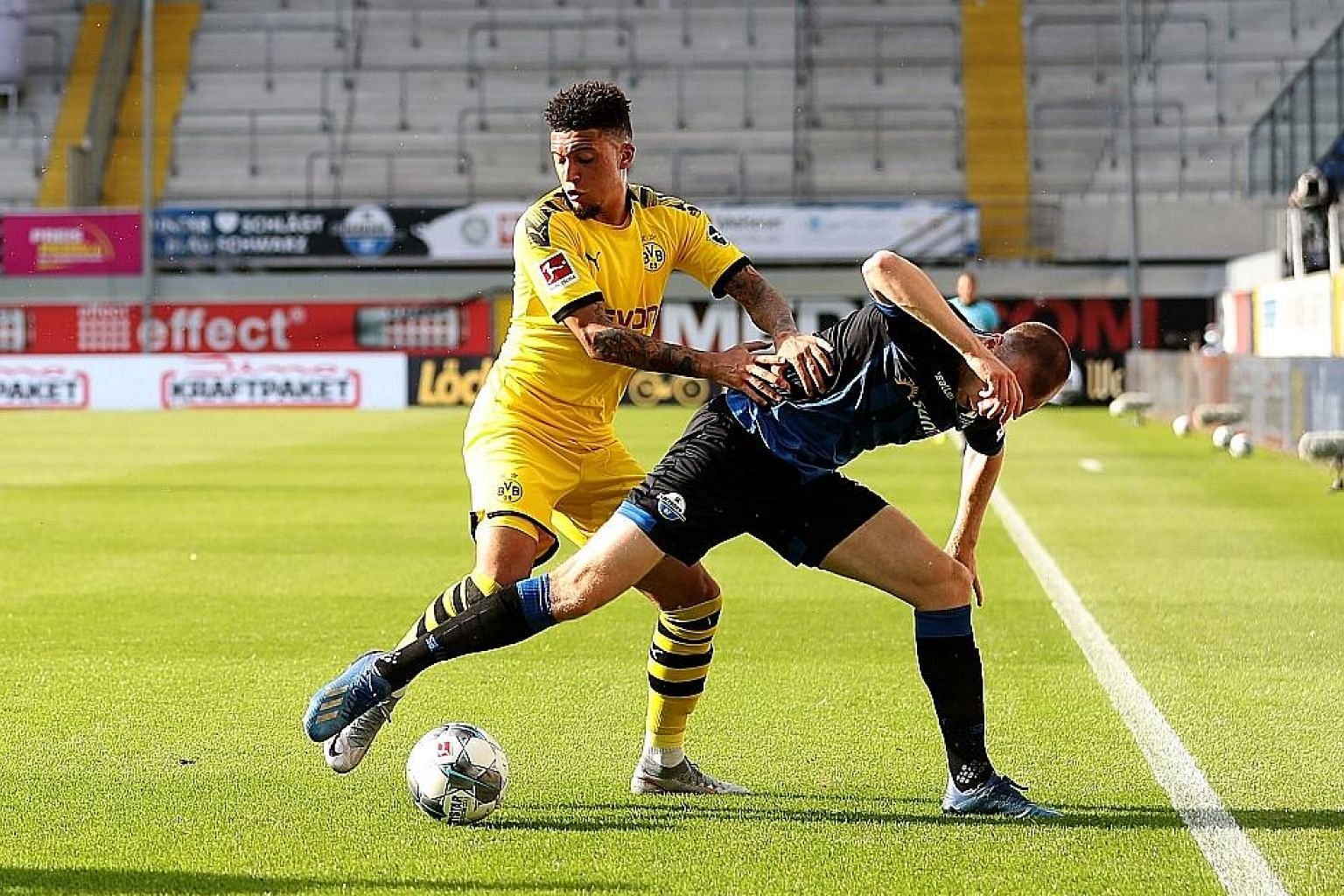 Jadon Sancho (left) fighting for the ball with Sebastian Schonlau of Paderborn in Dortmund's 6-1 win. The 20-year-old Englishman, who was let go by Manchester City, netted his first hat-trick for the Bundesliga side. PHOTO: EPA-EFE