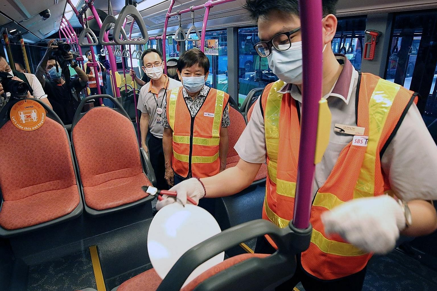 Transport Minister Khaw Boon Wan (centre) observing as a staff member removed a safe distancing notice from a seat on a bus at Ang Mo Kio Bus Interchange yesterday. PHOTO: LIANHE ZAOBAO