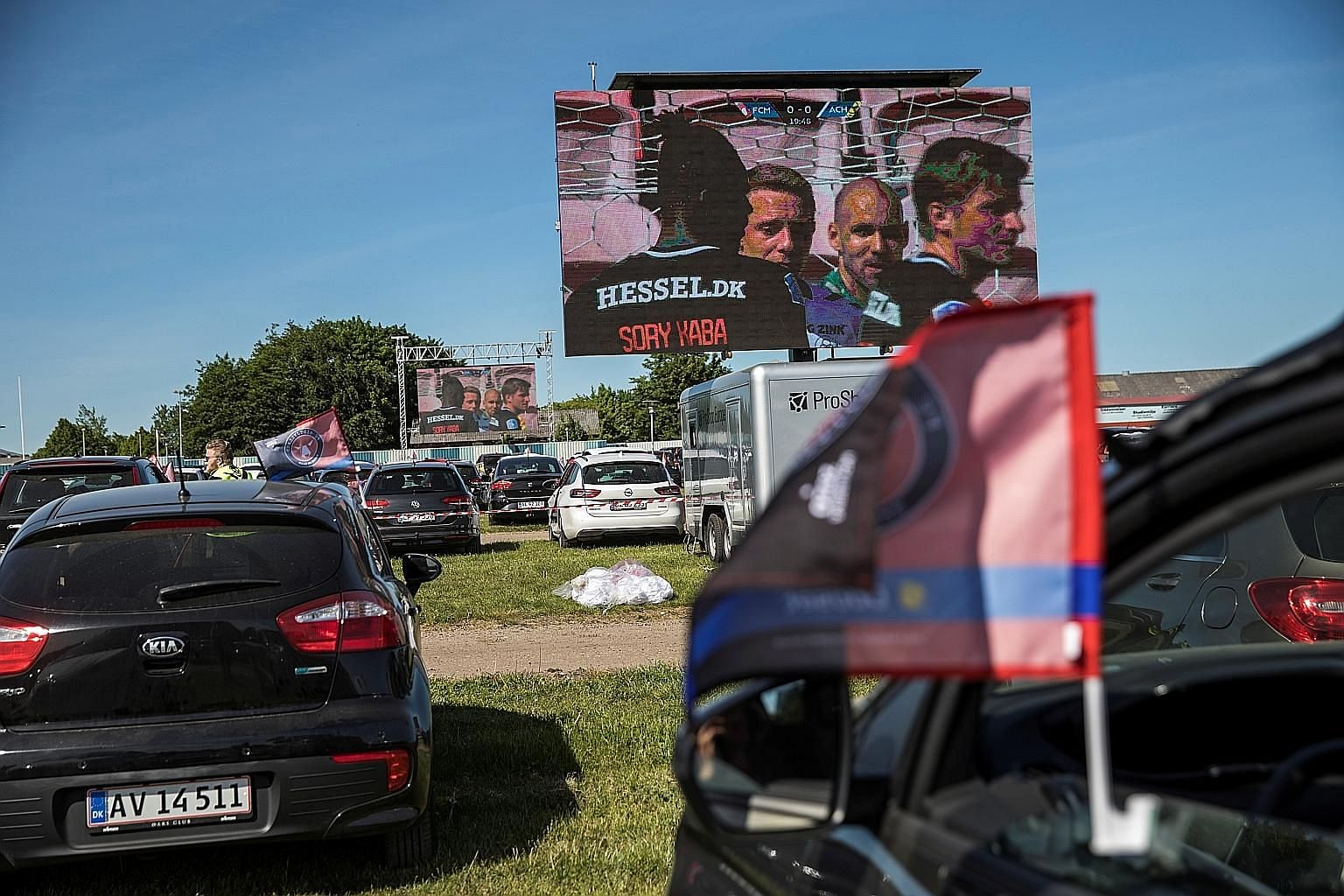 "Spectators in their cars at the parking lot of Midtjylland's MCH Arena watching a live video screening of the Danish Superliga match against Horsens on Monday. The ""drive-in"" was set up so that fans could get their football fix since spectators were"