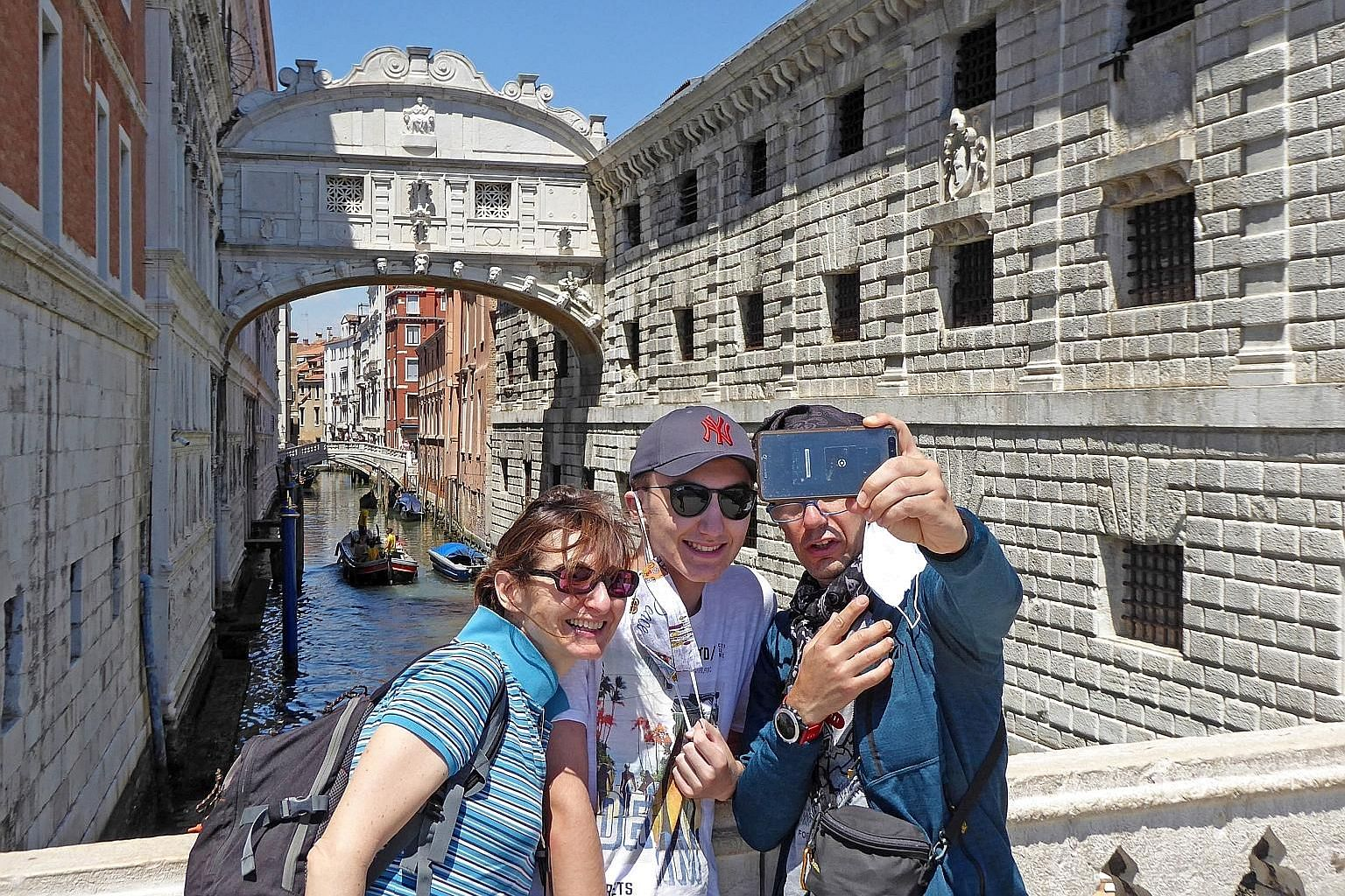Tourists on San Marco pier in Venice, Italy, with the Ponte dei Sospiri, or Bridge of Sighs, in the background, on Monday. People in the Veneto region are not obliged to wear face masks on the street as the country is gradually easing lockdown curbs