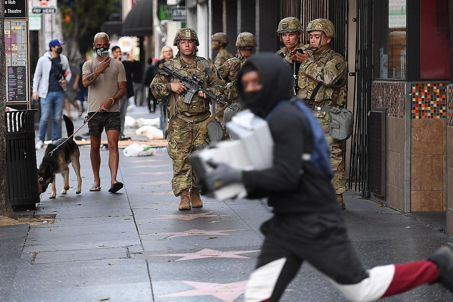 A looter running past National Guard personnel in Hollywood, California, on Monday. The protesters have comprised not just African Americans but to a large extent white people and also, by and large, young people. They have been mostly peaceful durin