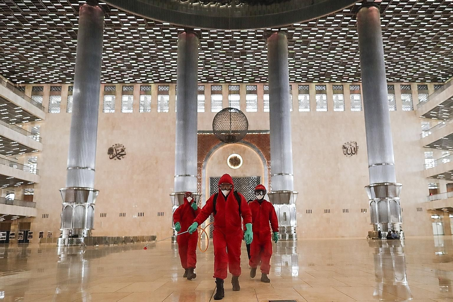 Disinfectant being sprayed at Istiqlal Mosque in Jakarta on Wednesday. Places of worship in the Indonesian capital can open their doors from today, as part of a transition phase over the next few weeks. The city administration can reinstate restricti
