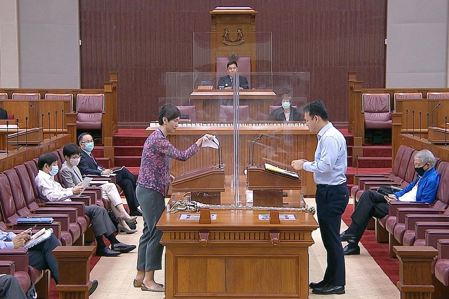 Manpower Minister Josephine Teo wiping down the microphone and podium after answering questions in Parliament yesterday as Minister of State for Manpower Zaqy Mohamad stepped up to speak. Perspex screens were set up in the House as part of safe dista
