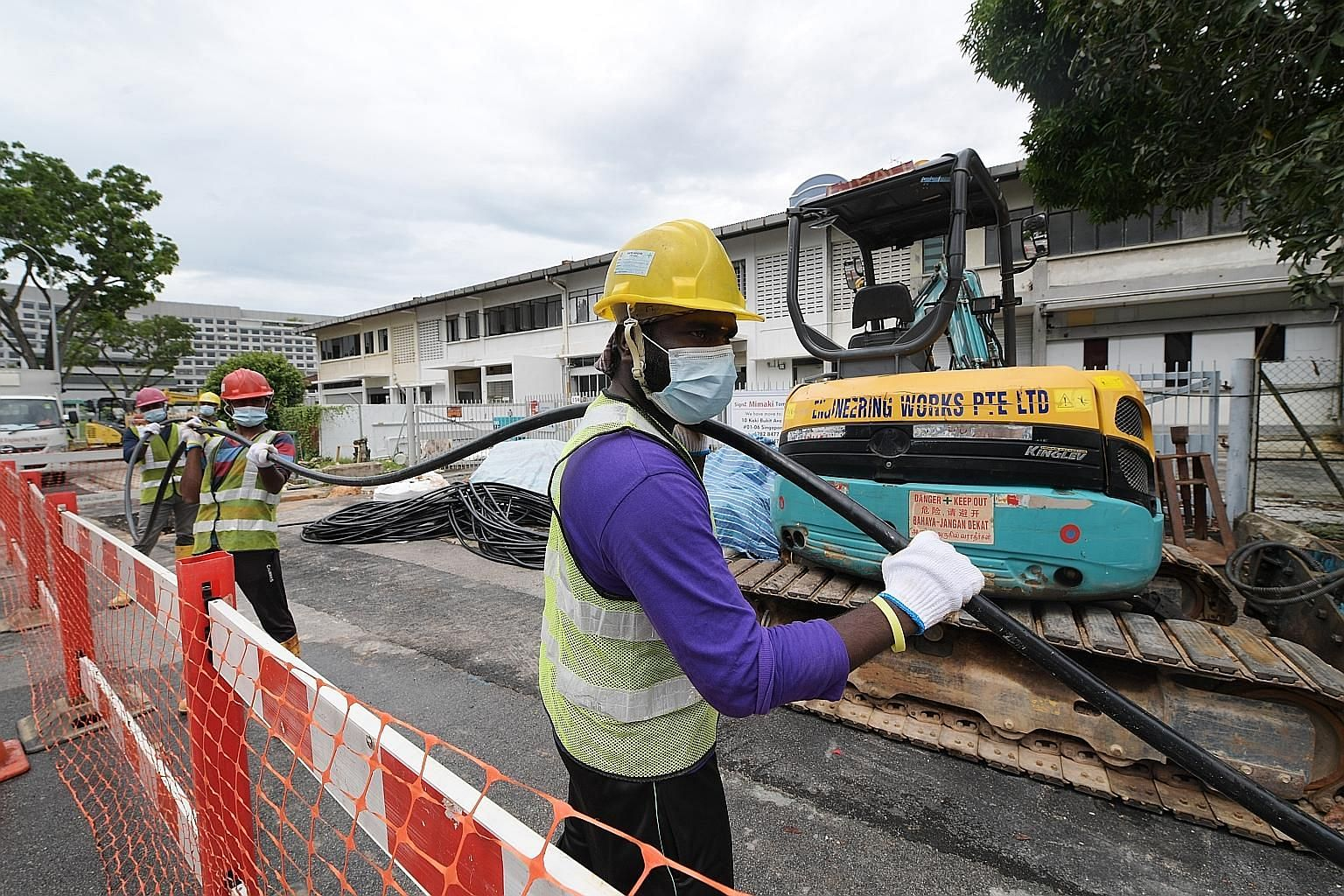 Workers from SP Group doing cabling work on May 13 to prepare a building in Genting Lane to house quarantined Covid-19 patients.