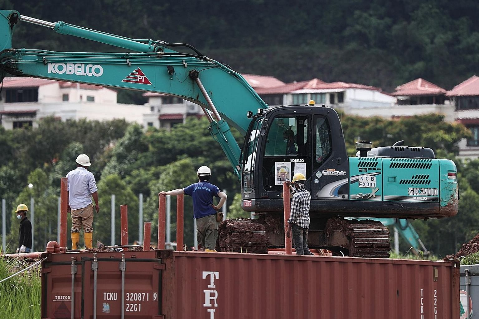 Workers at a site in Choa Chu Kang Grove yesterday. After consulting with the Health Ministry, the authorities will no longer require S-Pass and work permit holders in the construction sector who do not live in dormitories, work only in offices and d