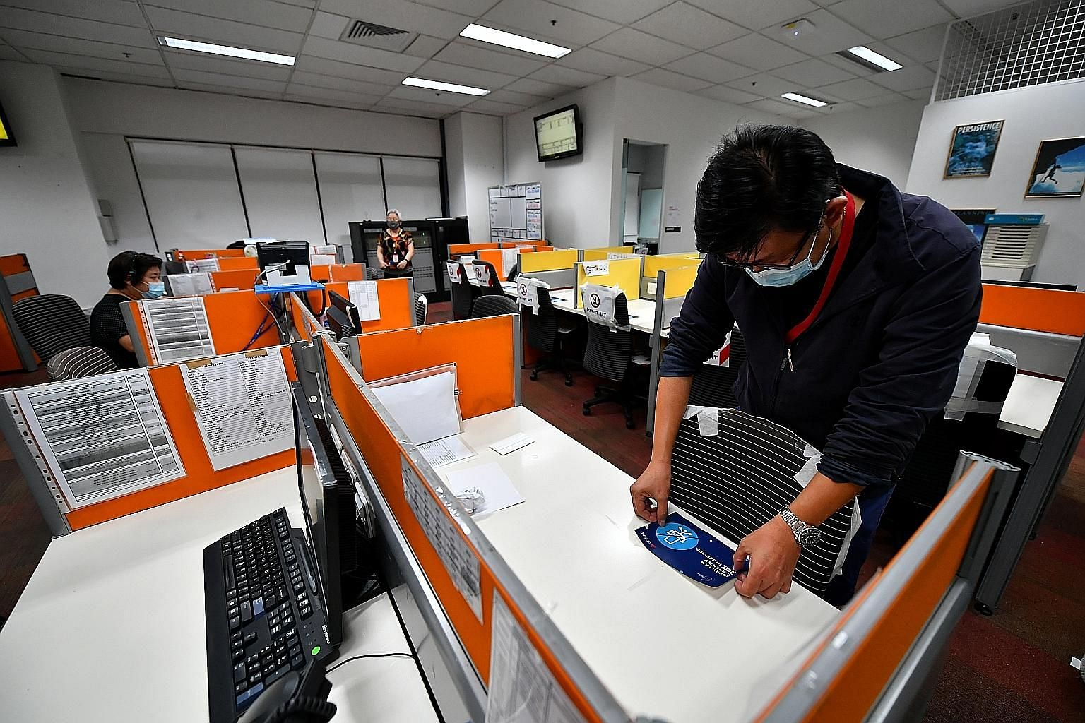 Mr Andrew Toh, 48, a senior manager at Synergy Graphics, pasting safe distancing decals at the contact centre of C&W Services last week. The Covid-19 pandemic has inadvertently created a worldwide experiment for remote work, but research shows that p