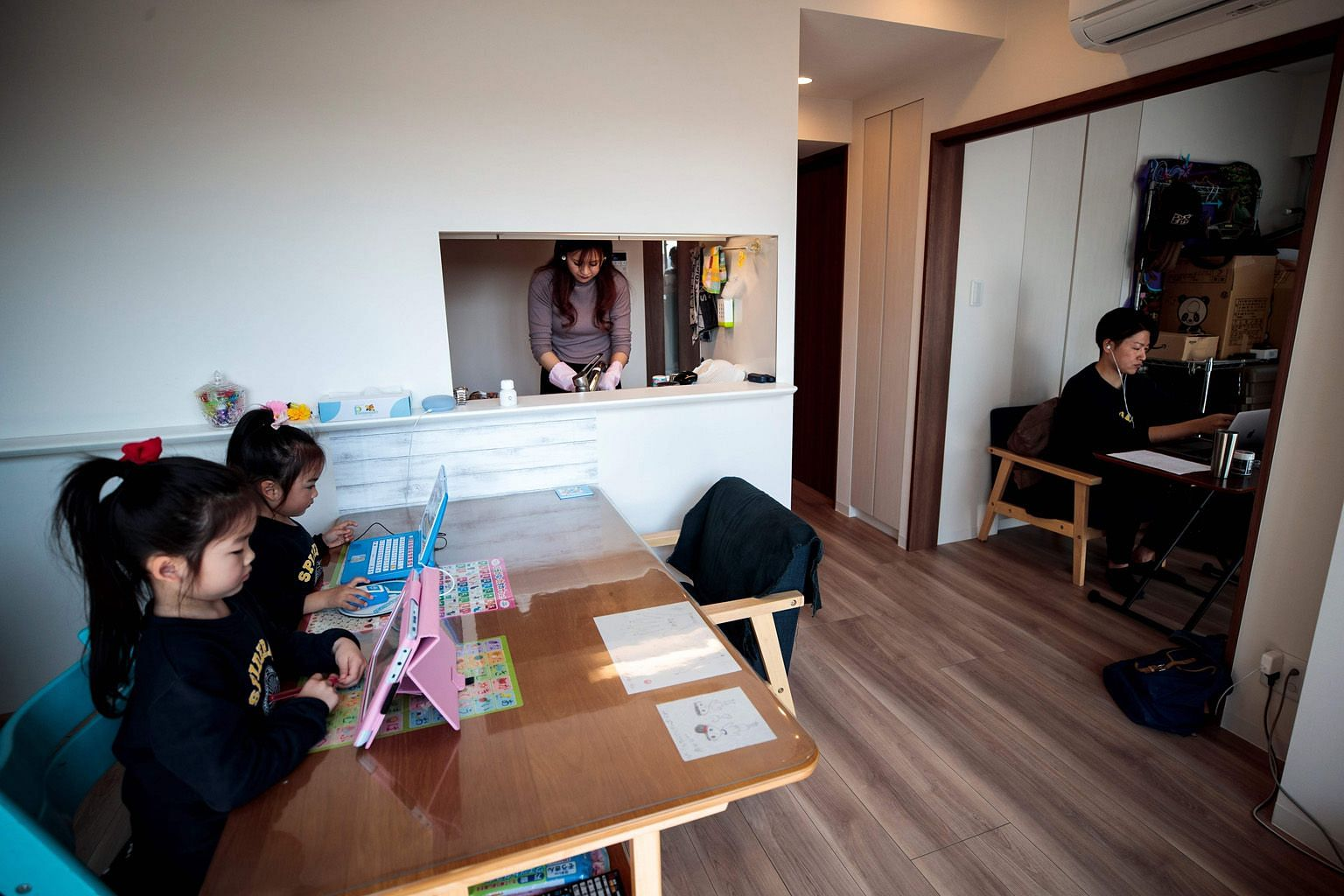 "Mr Yuki Sato, an employee in a start-up company, working from home in Tokyo while his wife Hitomi washes the dishes and his daughters do their homework. In Japan, many electronics firms have kept in place telework arrangements as the ""new normal"", af"