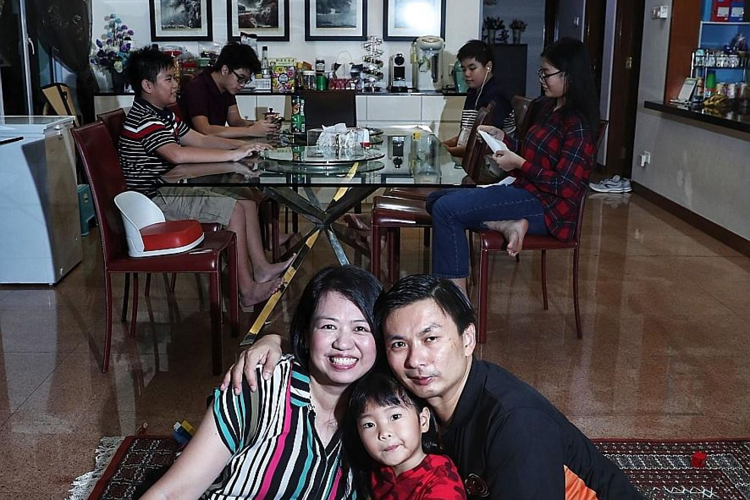 Madam Tay Hwee Ling and her husband Kelvin Lim adopted Mikaela (centre), five, whom they have taken care of since her birth. Seated behind them are the Lim's biological children, who are aged between 12 and 16. There have been a few foster parents li