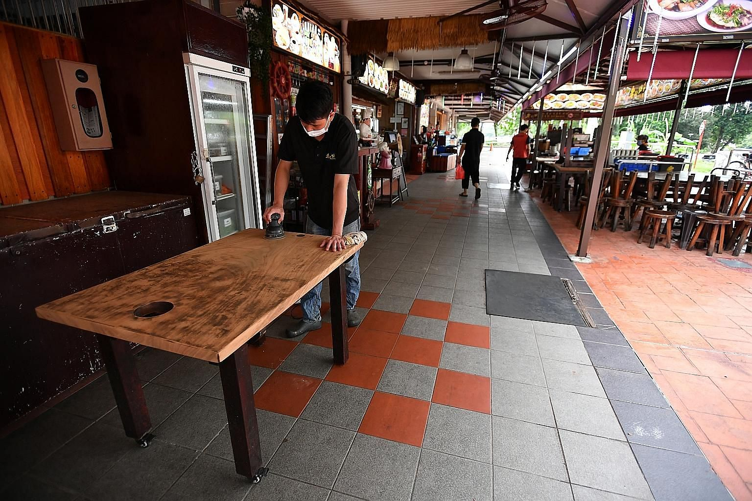 An employee of Olden Street Bak Kut Teh at Changi Village Hawker Centre cleaning the table yesterday, as eateries prepare to welcome diners from Friday, when dining in is allowed to resume.