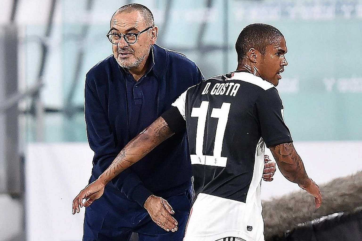 Juventus coach Maurizio Sarri with Douglas Costa after taking him off in the second leg of the Italian Cup semi-final against AC Milan last Friday.