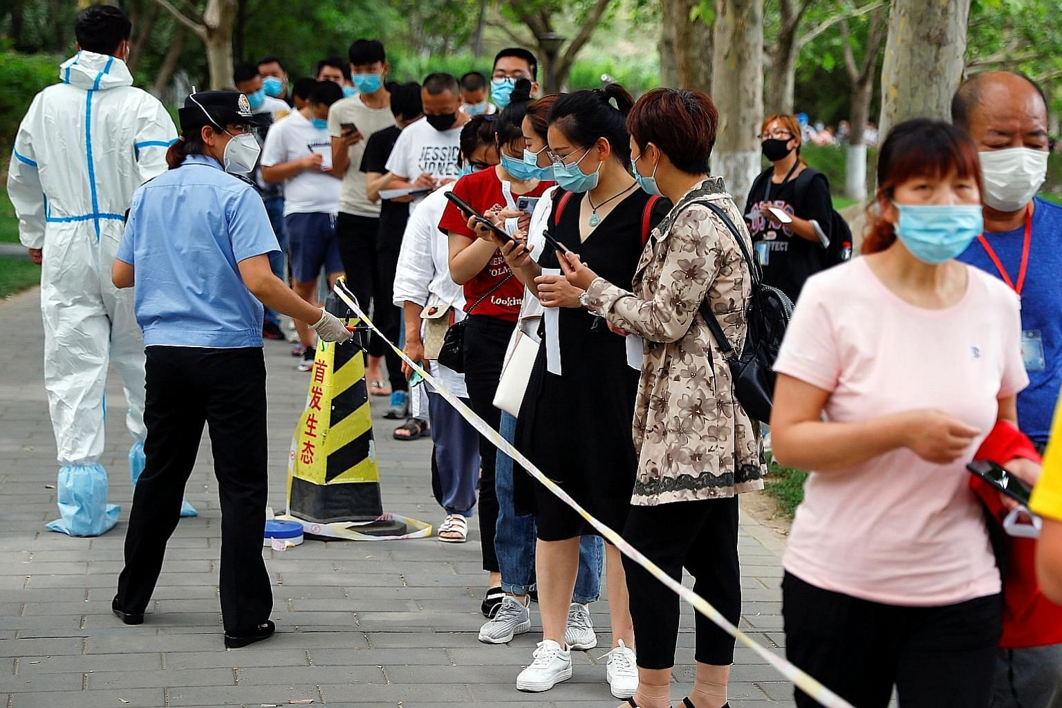 People lining up for a nucleic acid test in Fengtai district yesterday, after the outbreak in Beijing. The city has classified at least one community as high risk and subjected its residents to quarantine, and 32 others as medium risk. PHOTO: REUTERS