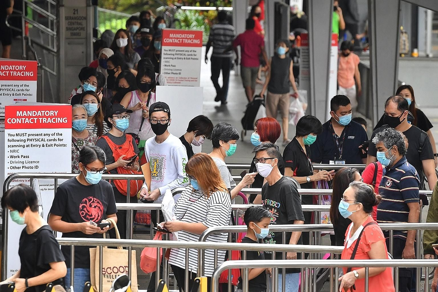 People queueing to use the SafeEntry system for contact tracing before entering Nex mall in Serangoon yesterday, when retailers across Singapore saw a steady flow of customers that lasted all day in some spots. ST PHOTO: CHONG JUN LIANG