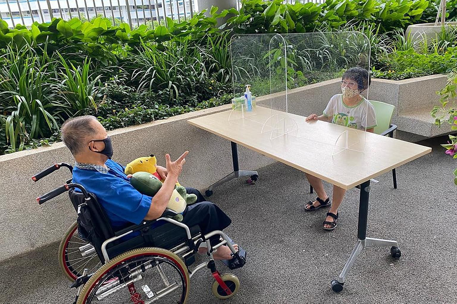 Ms Grace Ang, 39, visiting her father Ang Tiak Huat, 72, at NTUC Health Nursing Home (Geylang East). Clear acrylic partitions separating visitors from residents help to minimise the risk of droplets spreading. PHOTO: NTUC HEALTH