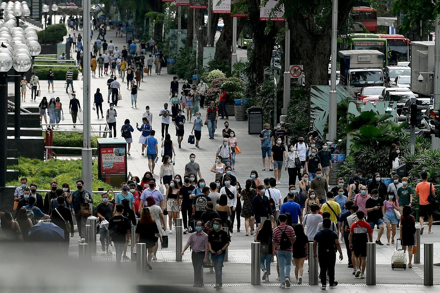 The city came alive again yesterday, the first day of phase two of Singapore's reopening. (From top) People thronging the streets of Orchard Road, albeit wearing face masks; shoppers leaving Tangs department store with their purchases; and customers