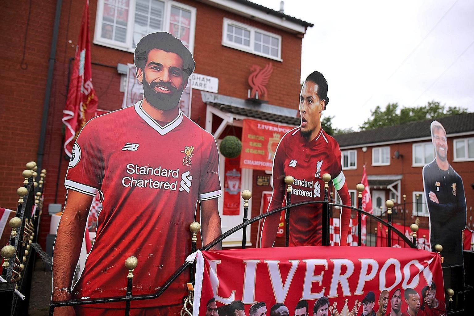 Cut-outs of (from left) Liverpool's Mohamed Salah, Virgil van Dijk and manager Jurgen Klopp are seen outside the house of a Reds fan. PHOTO: REUTERS