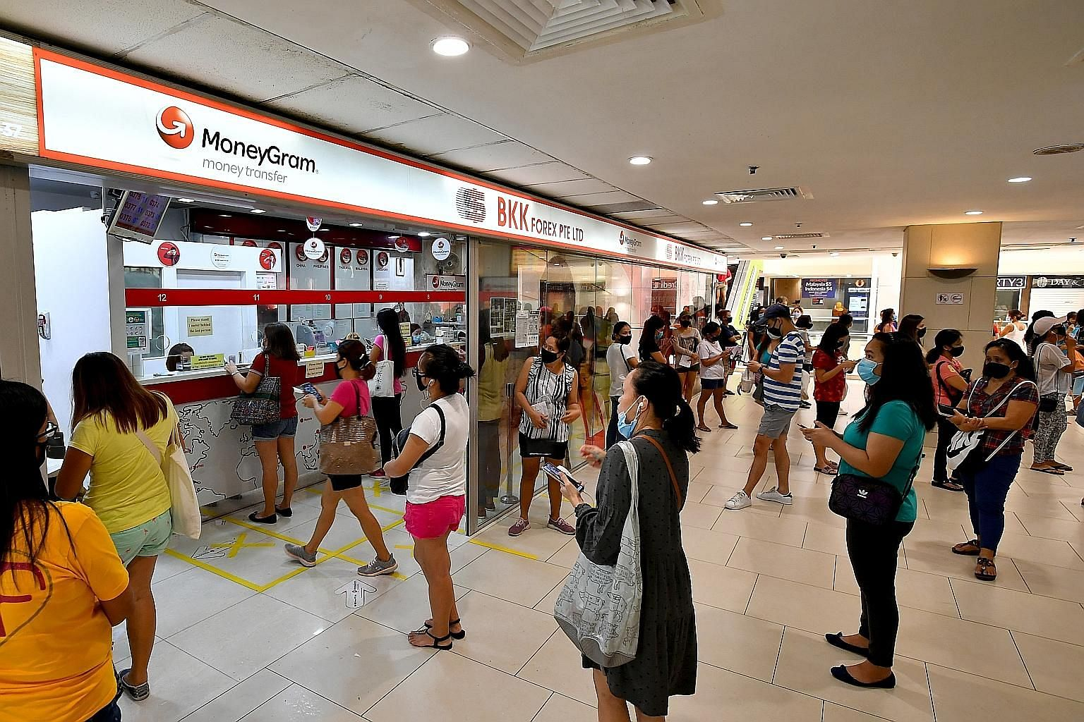 People queueing for remittance services at Lucky Plaza on May 31, even before the circuit breaker period had ended. Many domestic workers are their families' breadwinners, and sending money home could mean their loved ones being able to have their ne