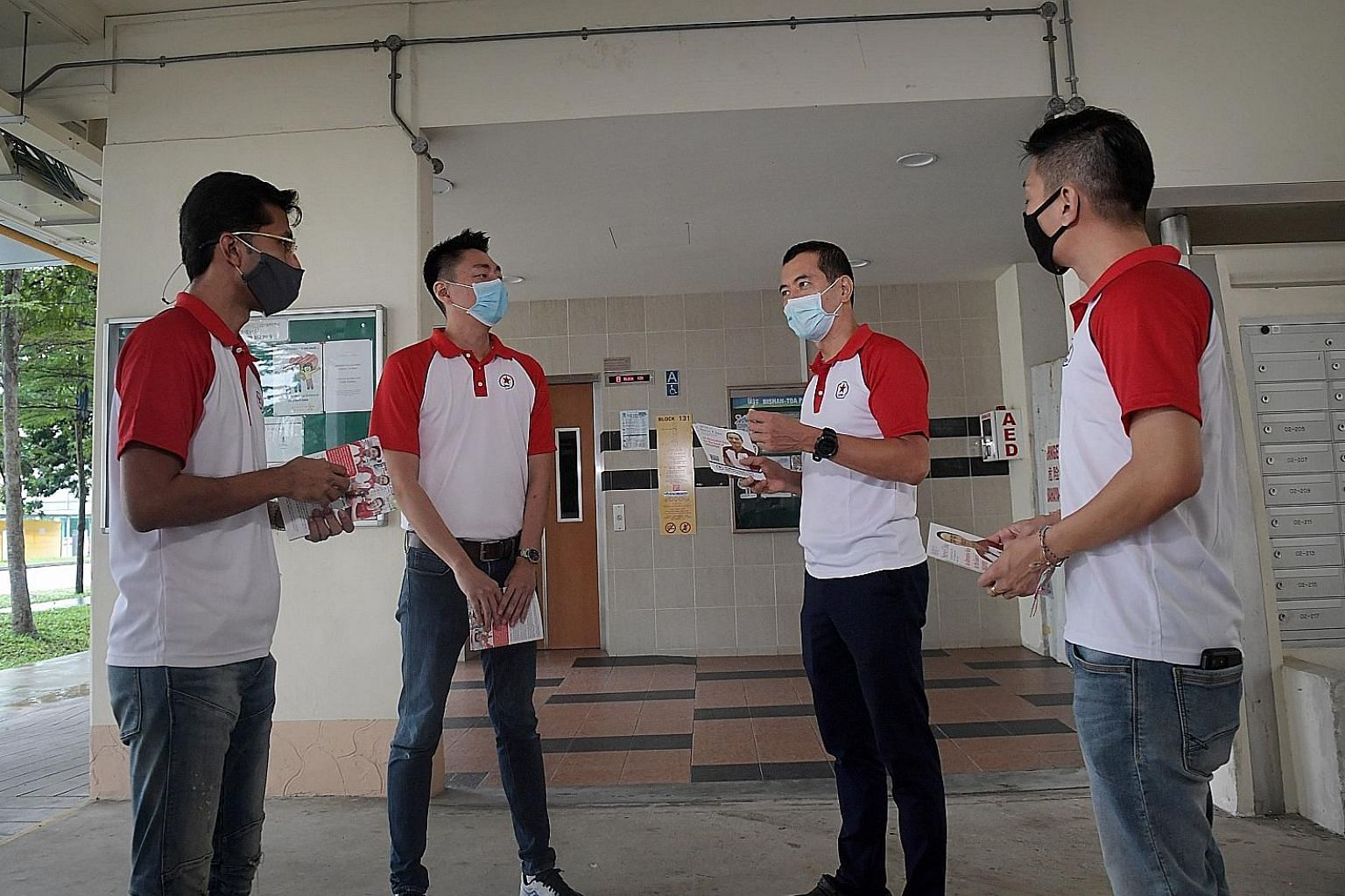 From left: Singapore People's Party candidates Osman Sulaiman, Melvyn Chiu, Steve Chia and Williiamson Lee preparing to hand out fliers and meet residents at Block 131, Bishan Street 12, yesterday.