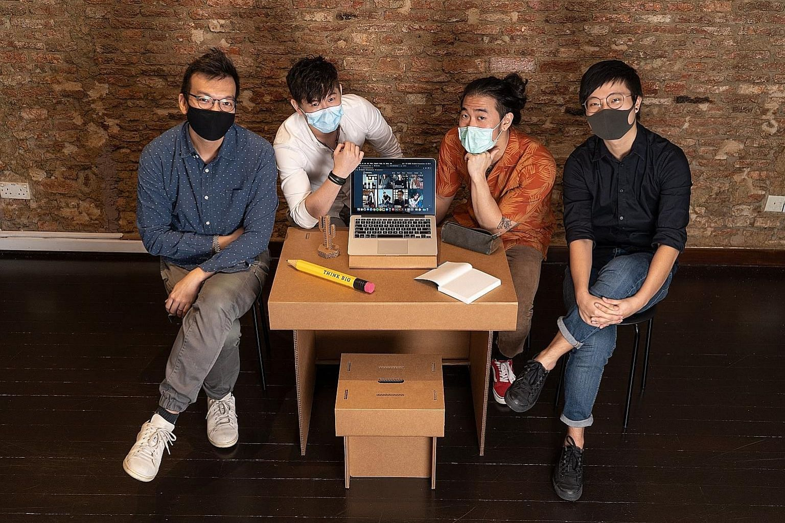From left: Design director John Chan, design intern Scott Lee, content strategist Christian Sng, and experience and 3D designer Teo Kiah Sheng from strategic design consultancy Chemistry with the #HBLTable, which is made of sturdy double-wall cardboa