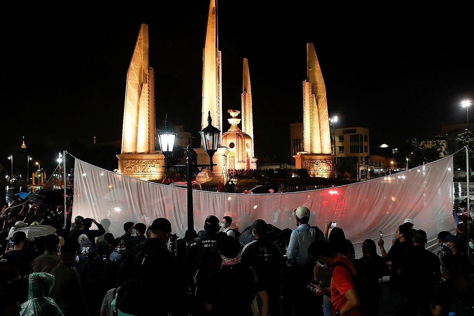 Thai pro-democracy protesters place a white screen in front of the Democracy Monument in Bangkok, calling yesterday for change to the constitution on the 88th anniversary of a revolt that ended Thailand's absolute monarchy.