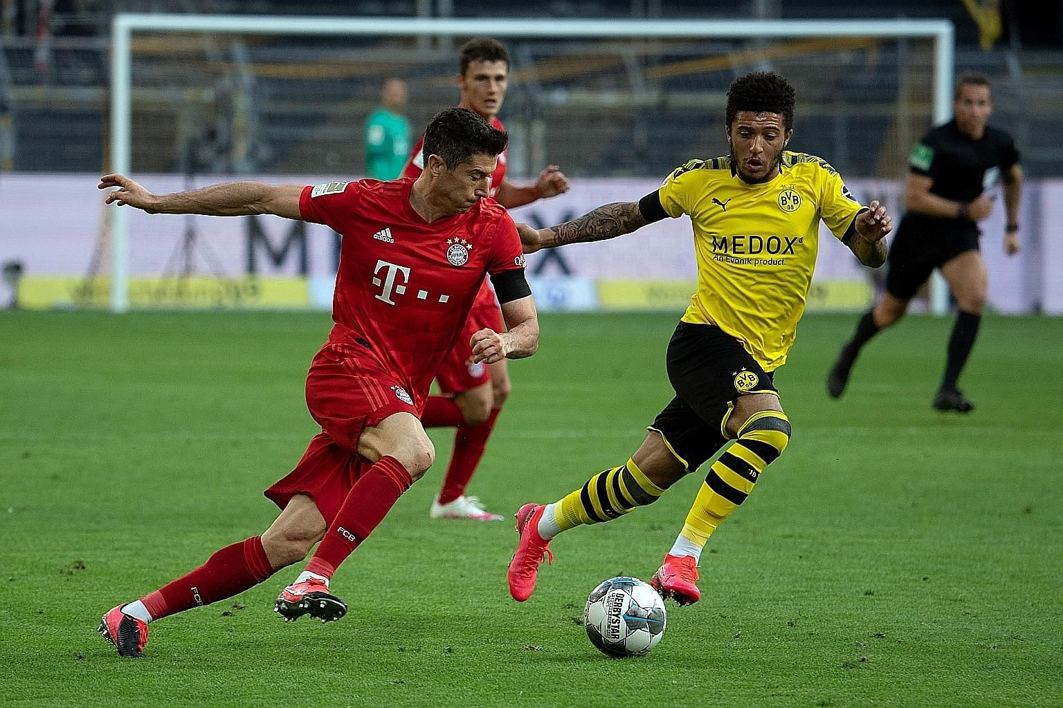 Bayern's Robert Lewandowski taking on Dortmund's Jadon Sancho. The latest €4.4 billion Bundesliga deal represents the first drop in the value of a new rights package since 2002.