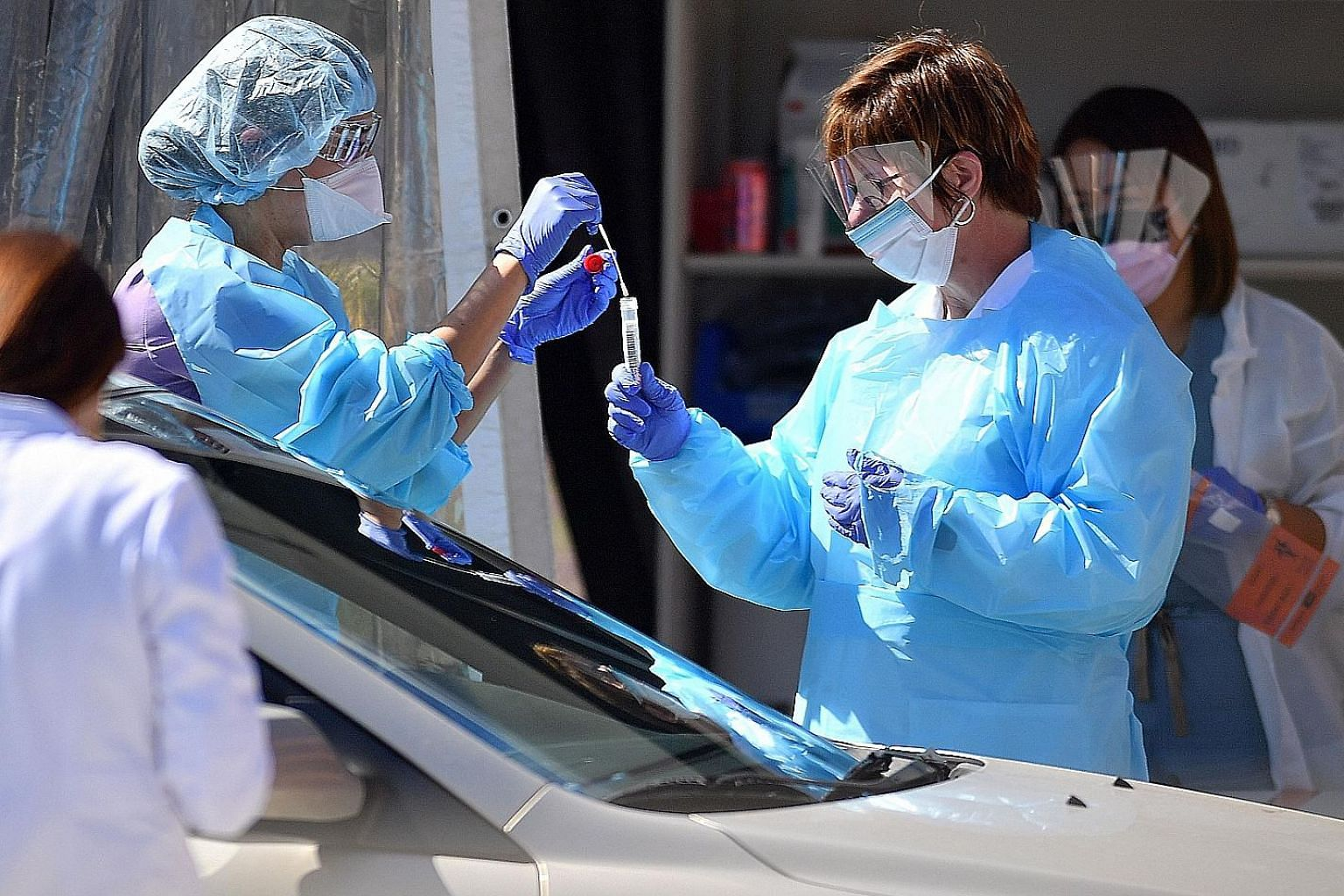 Medical workers collecting samples at a drive-through testing facility in San Francisco in March. The United States is among countries that have administered saliva tests to detect Covid-19. PHOTO: AGENCE FRANCE-PRESSE