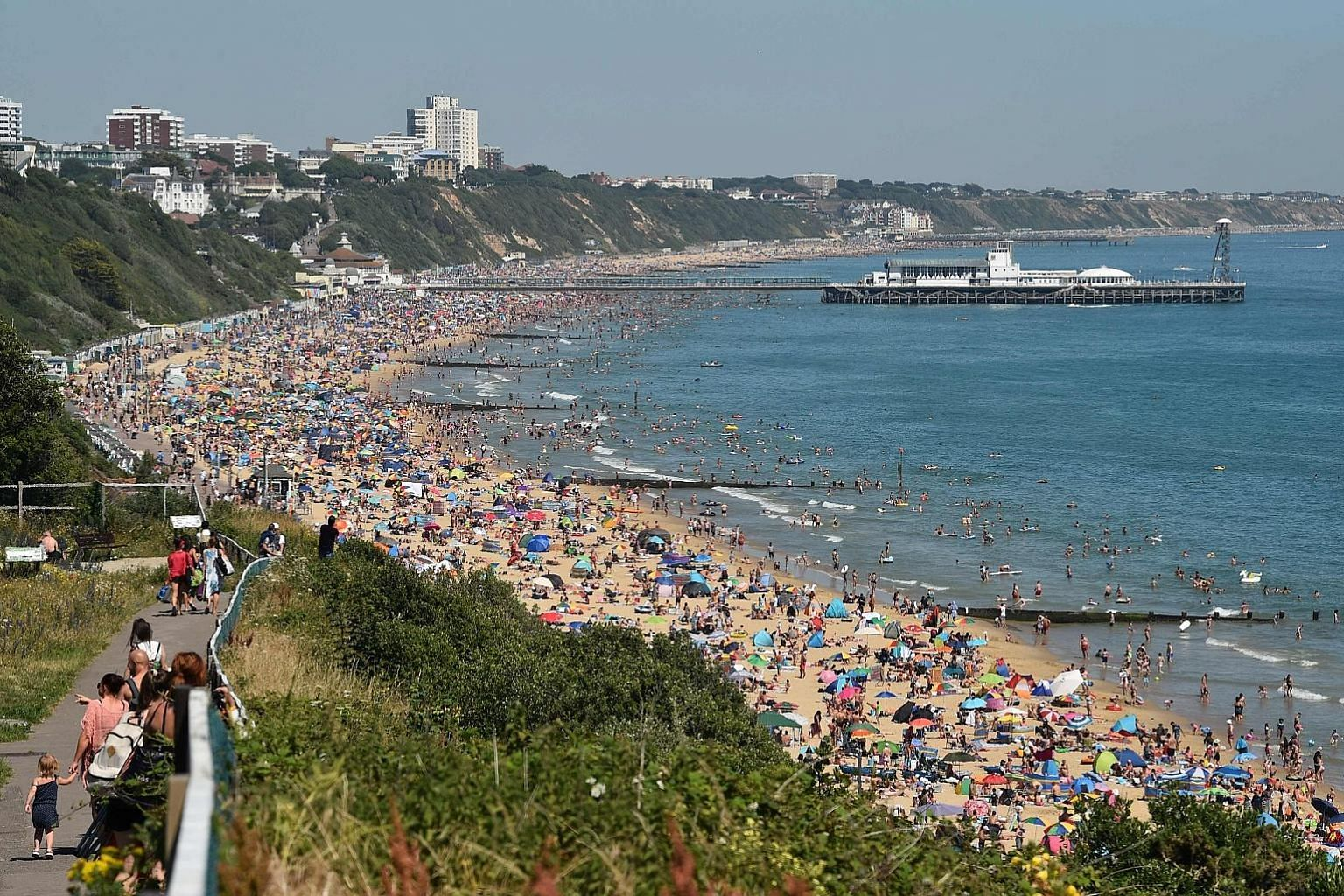 Beachgoers in Bournemouth on Thursday. With beaches packed, Britain's chief medical officer warned of the risk of infection.